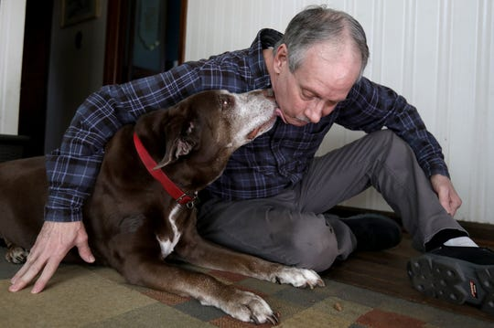 Brad Stottlemyer, 65 of Dearborn Heights with his 11-year-old chocolate lab mix Misty in their home on Thursday, March 7, 2019. 