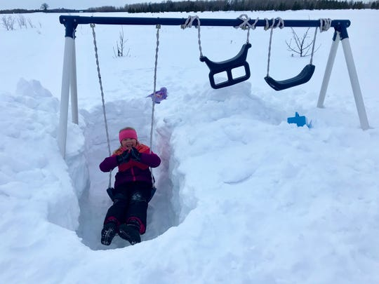 Allie Goulet, 5, has to take special measures to go swinging in Sault Ste. Marie, where the snow, a week before spring, is still deep.