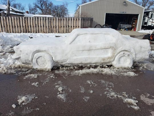 The Blundell family of Chadron, Nebraska, last weekend capitalized on a snowstorm to sculpt a replica of the 1967 Ford Mustang GTA, the rear of which is visible in their garage.