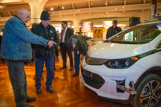 Jay Harris, 77, of Plymouth and The Henry Ford antique vehicle specialist Gordon Michael, 66, of Oak Park check out GM's first self-driving Bolt EV while GM President Mark Reuss speaks in the background Tuesday at the Henry Ford Museum in Dearborn.