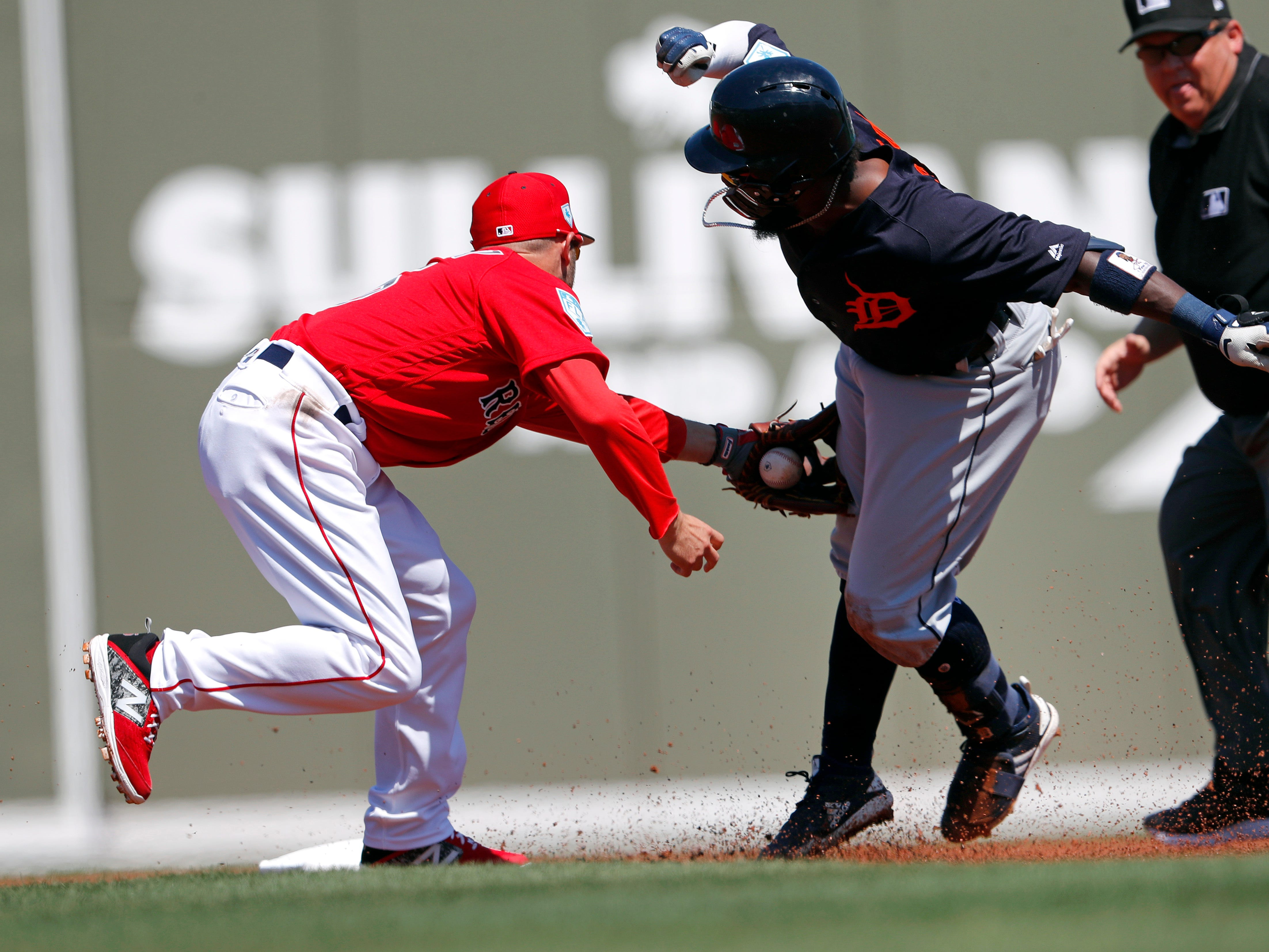 The Tigers' Josh Harrison is tagged out at second by Boston Red Sox second baseman Dustin Pedroia as he tries to stretch a single in the first inning.