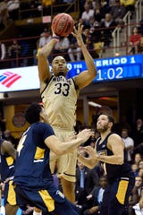 Wofford forward Cameron Jackson (33) shoots over UNC-Greensboro forward Kyrin Galloway (14) and guard Demetrius Troy (11) in the first half.