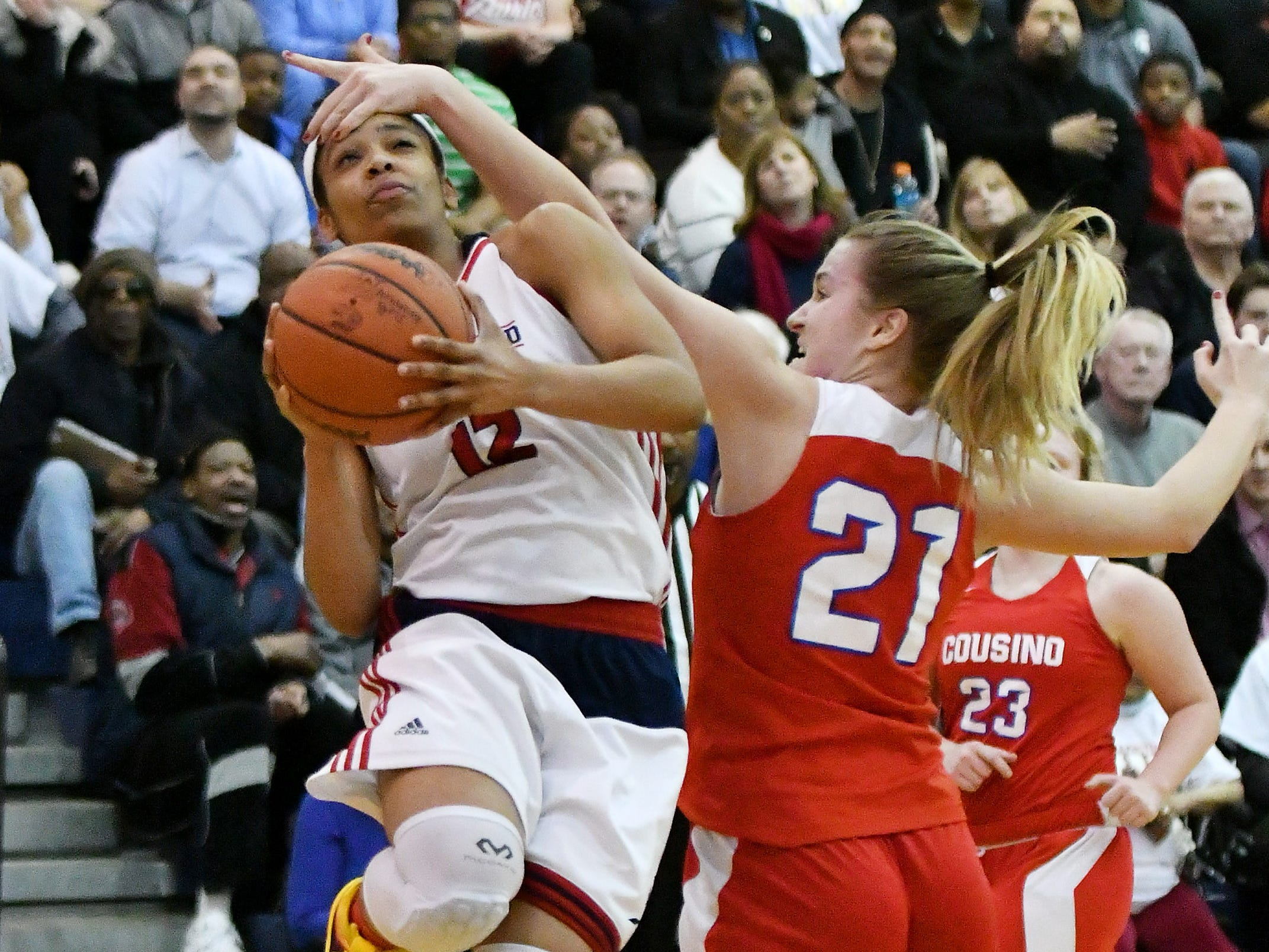 Warren Cousino's Olivia Jolliffe fouls Southfield A&T's Cheyenne McEvans in the 67-30 Southfield A&T victory in the regional semifinals in Southfield, Mich. on March 11, 2019.