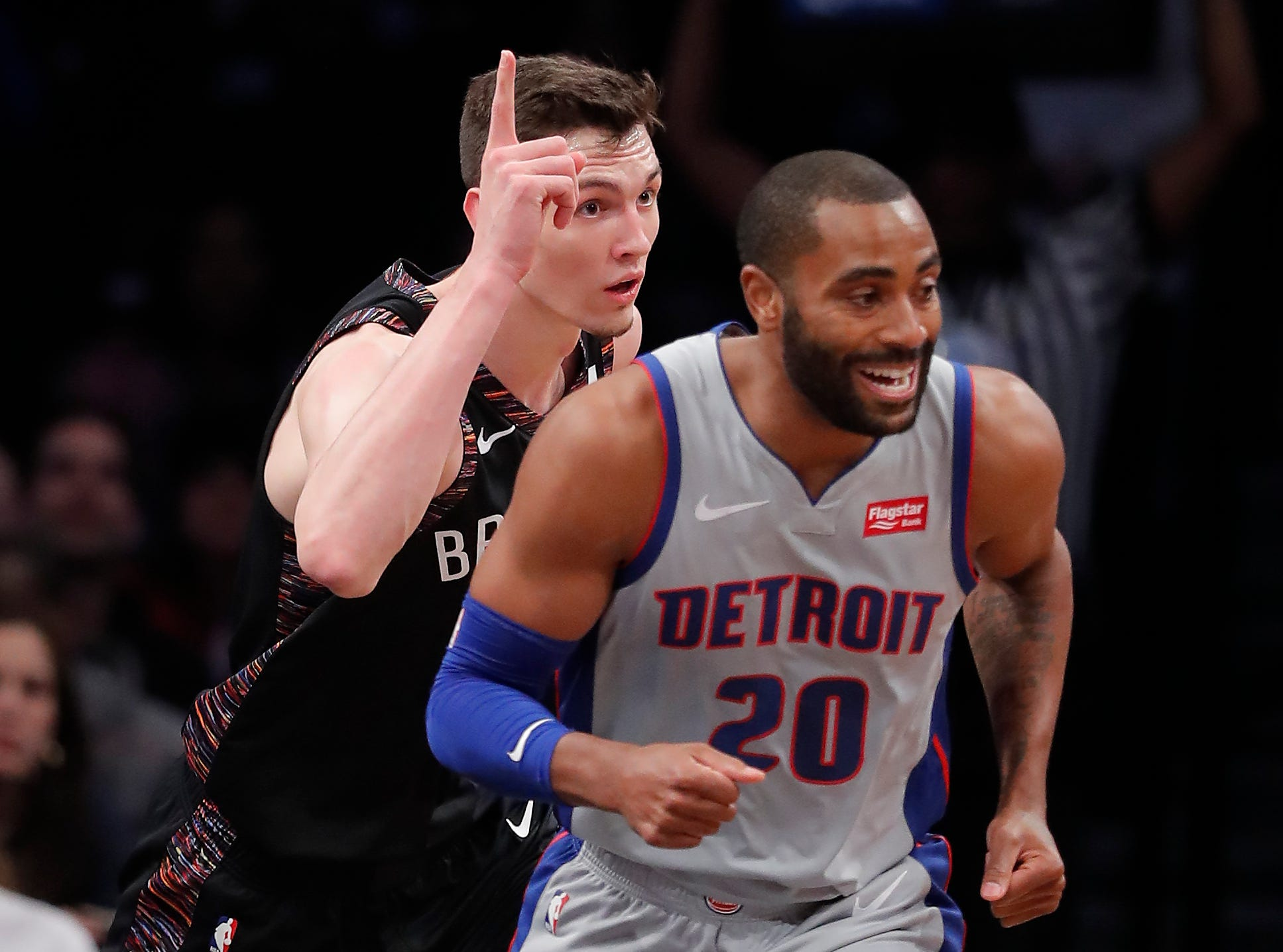 Brooklyn Nets forward Rodions Kurucs, left, reacts after scoring against the Detroit Pistons during the first quarter.