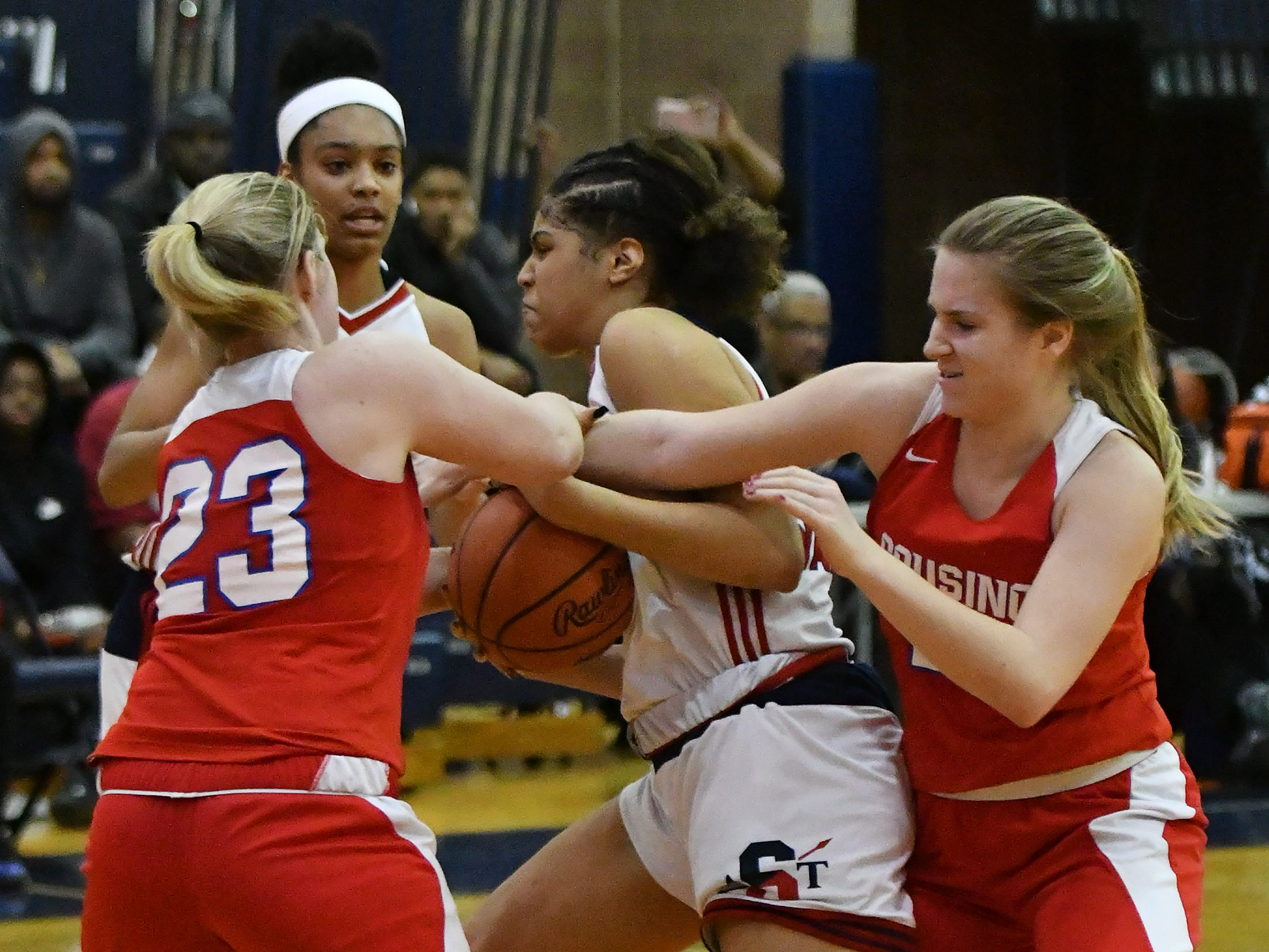 Southfield A&T's Jasmine Worthy tries to hold onto the ball between Warren Cousino's Olivia Joliffe, right, and Kate McArthur (23) in the second half.