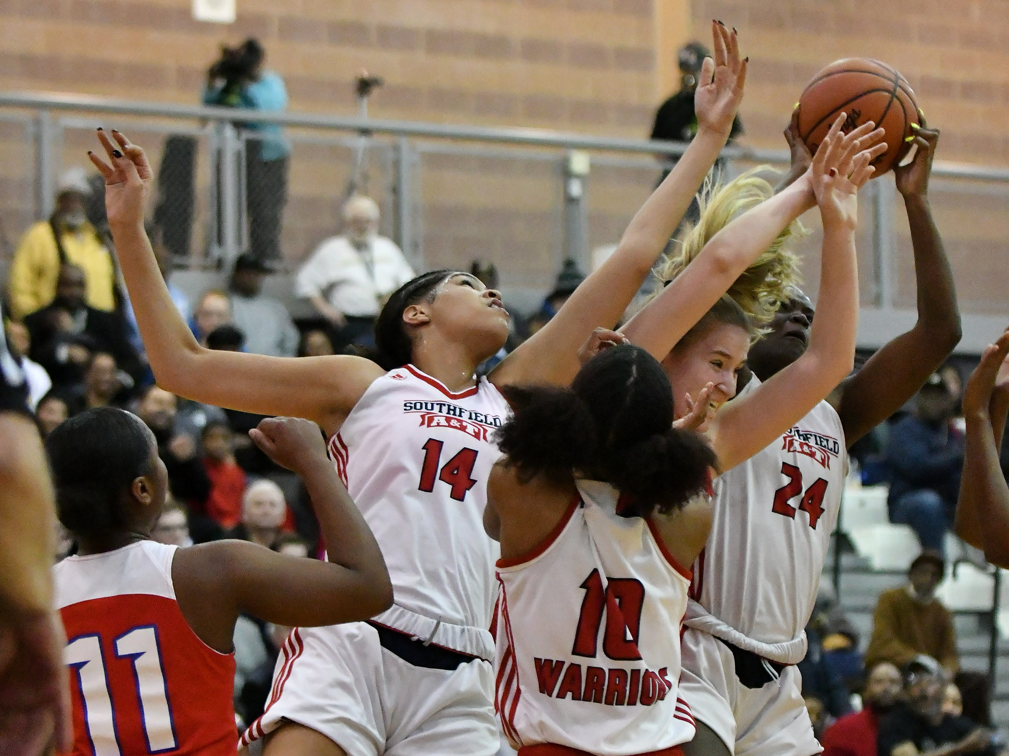Southfield A&T's Jasmine Worthy (14), Alexis Johnson (24) and Essence Pickett (10) surround Warren Cousino's Olivia Joliffe in the first half.