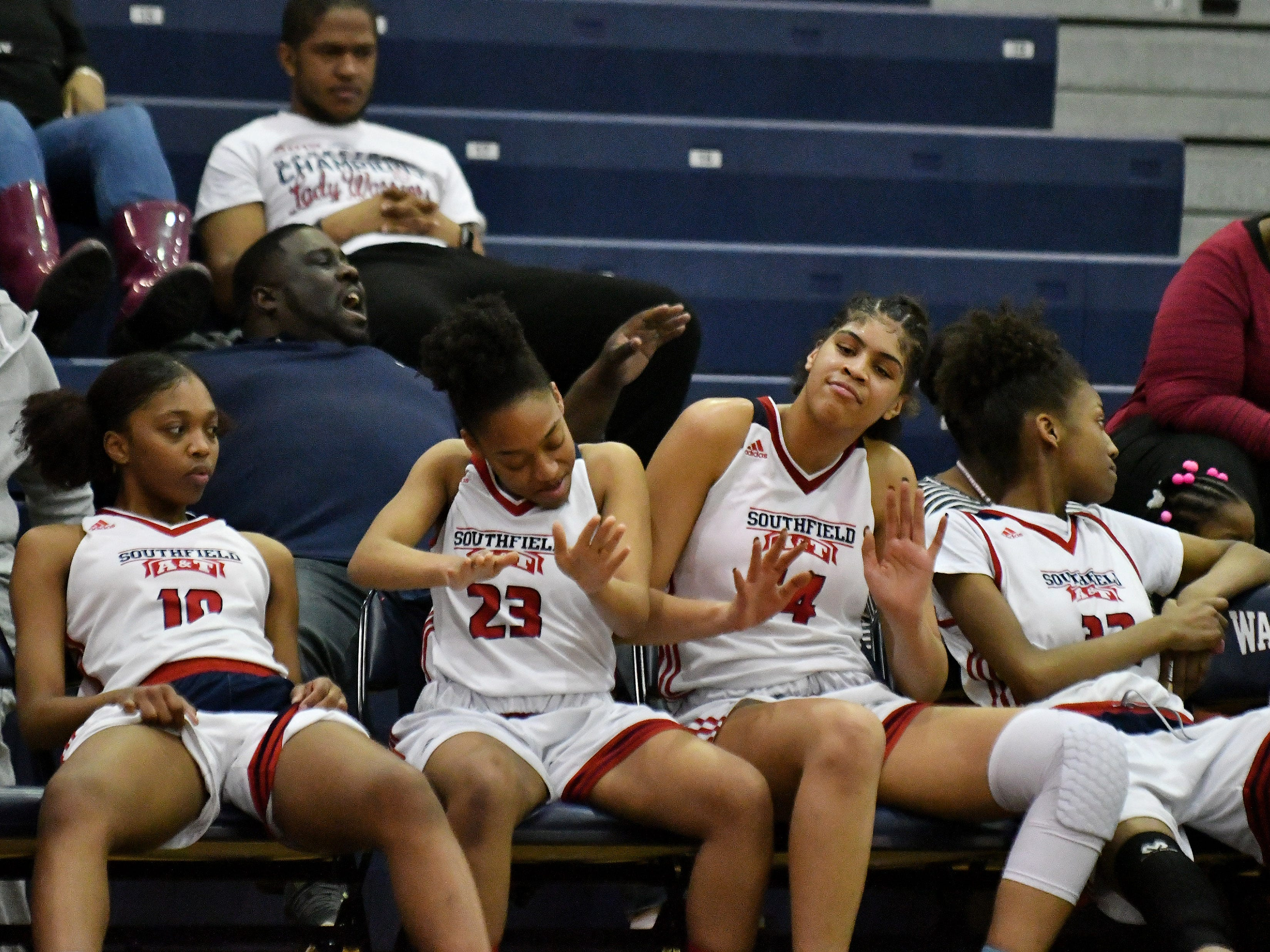 Southfield A&T's Rachel Hall (23) and Jasmine Worthy (14) do a little chair dancing on the bench in the second half.