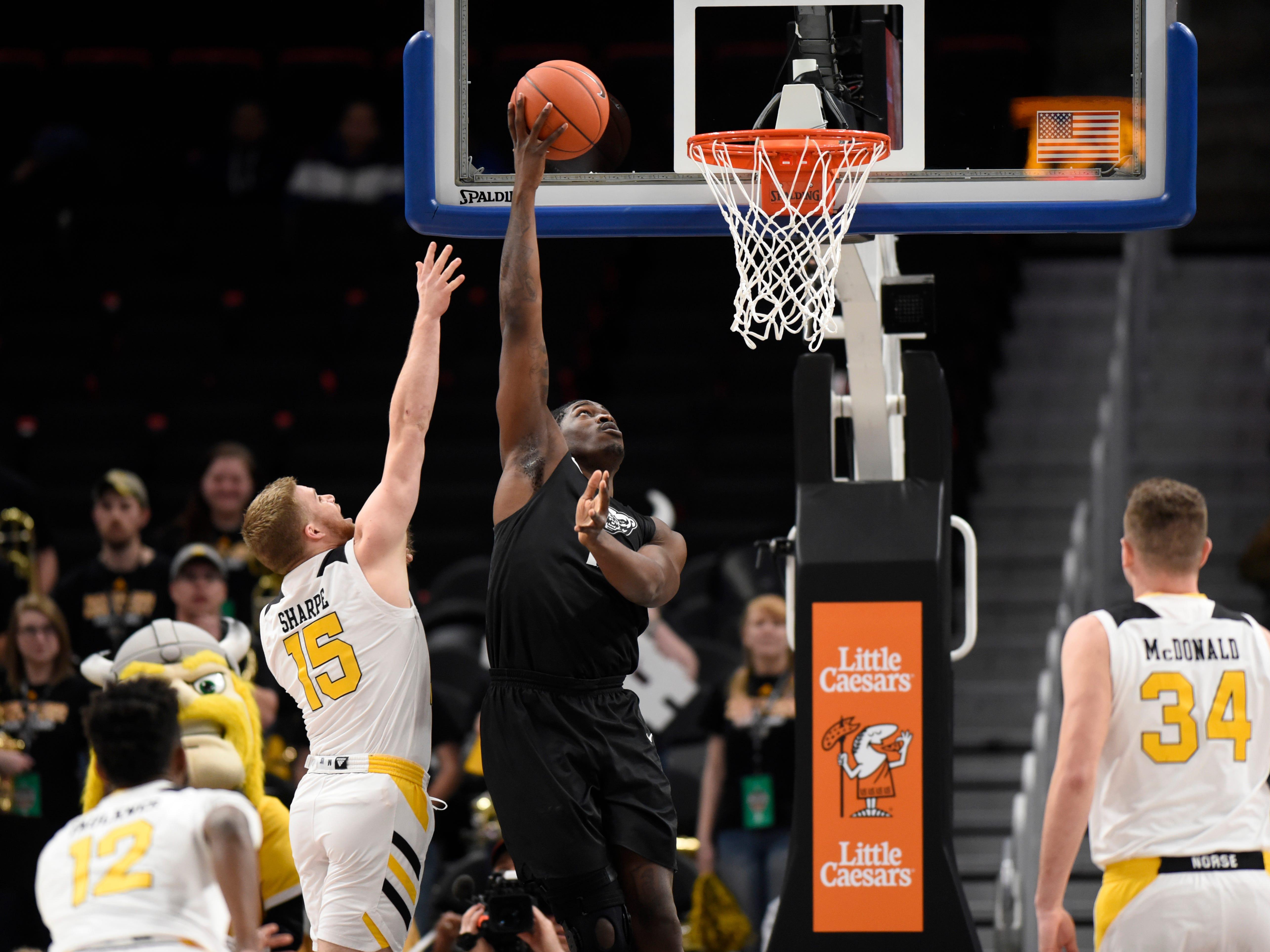 Oakland Golden Grizzlies forward Xavier Hill-Mais, right, puts up a shot over Northern Kentucky Norse guard Tyler Sharpe during the first half.