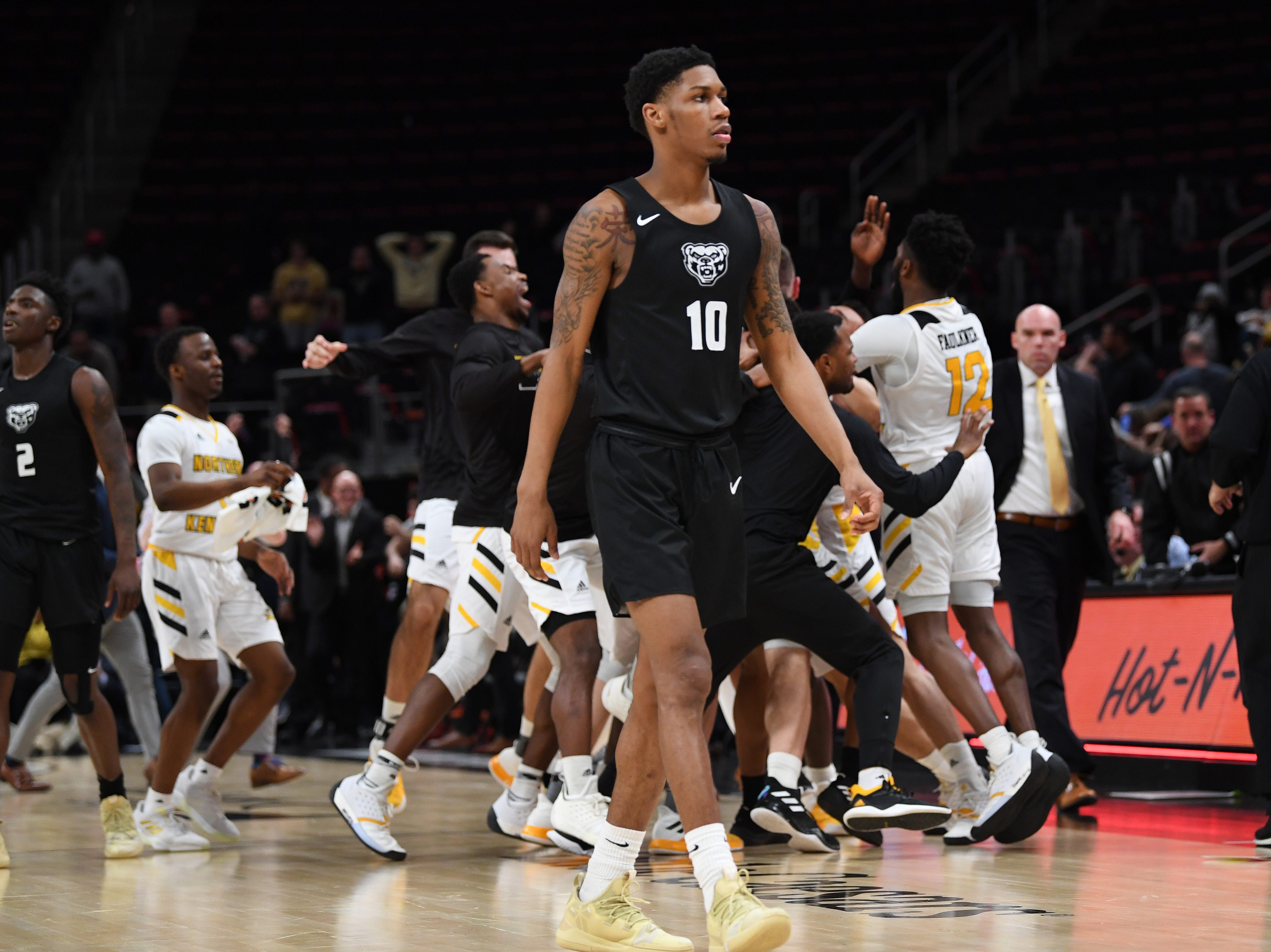 The Northern Kentucky Norse celebrate their victory as Oakland Golden Grizzlies guard Karmari Newman walks off the court at Little Caesars Arena in Detroit, Monday, Mar. 11, 2019.  Northern Kentucky defeated Oakland 64-63.