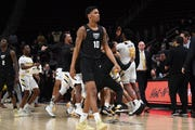 The Northern Kentucky Norse celebrate their 64-63 Horizon League tournament semifinal victory as Oakland Golden Grizzlies guard Karmari Newman walks off the court Monday at Little Caesars Arena.