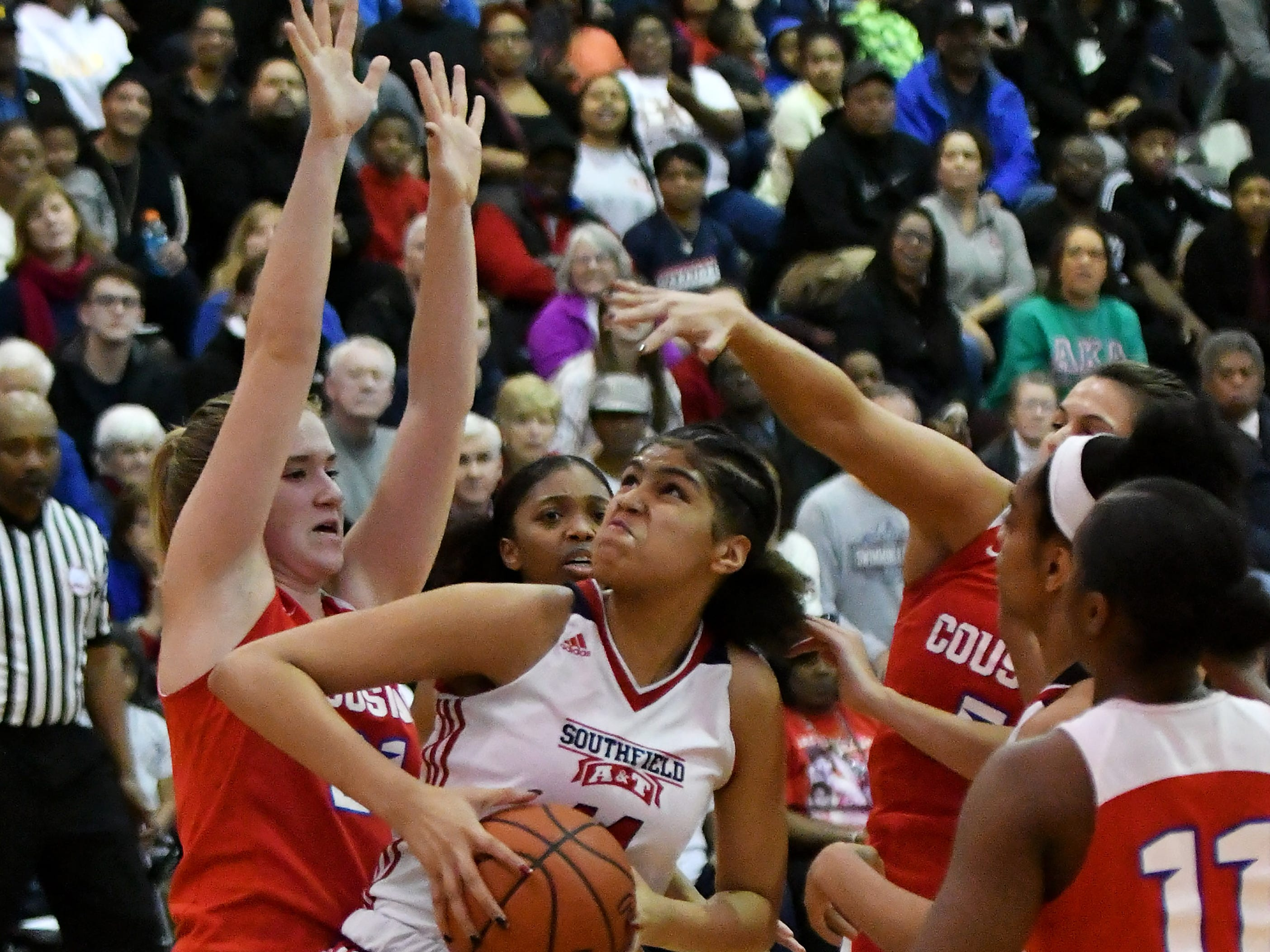 Southfield A&T's Jasmine Worthy pulls down a rebound and is about to put it back up while Warren Cousino's Olivia Joliffe, left, guards her in the first half.