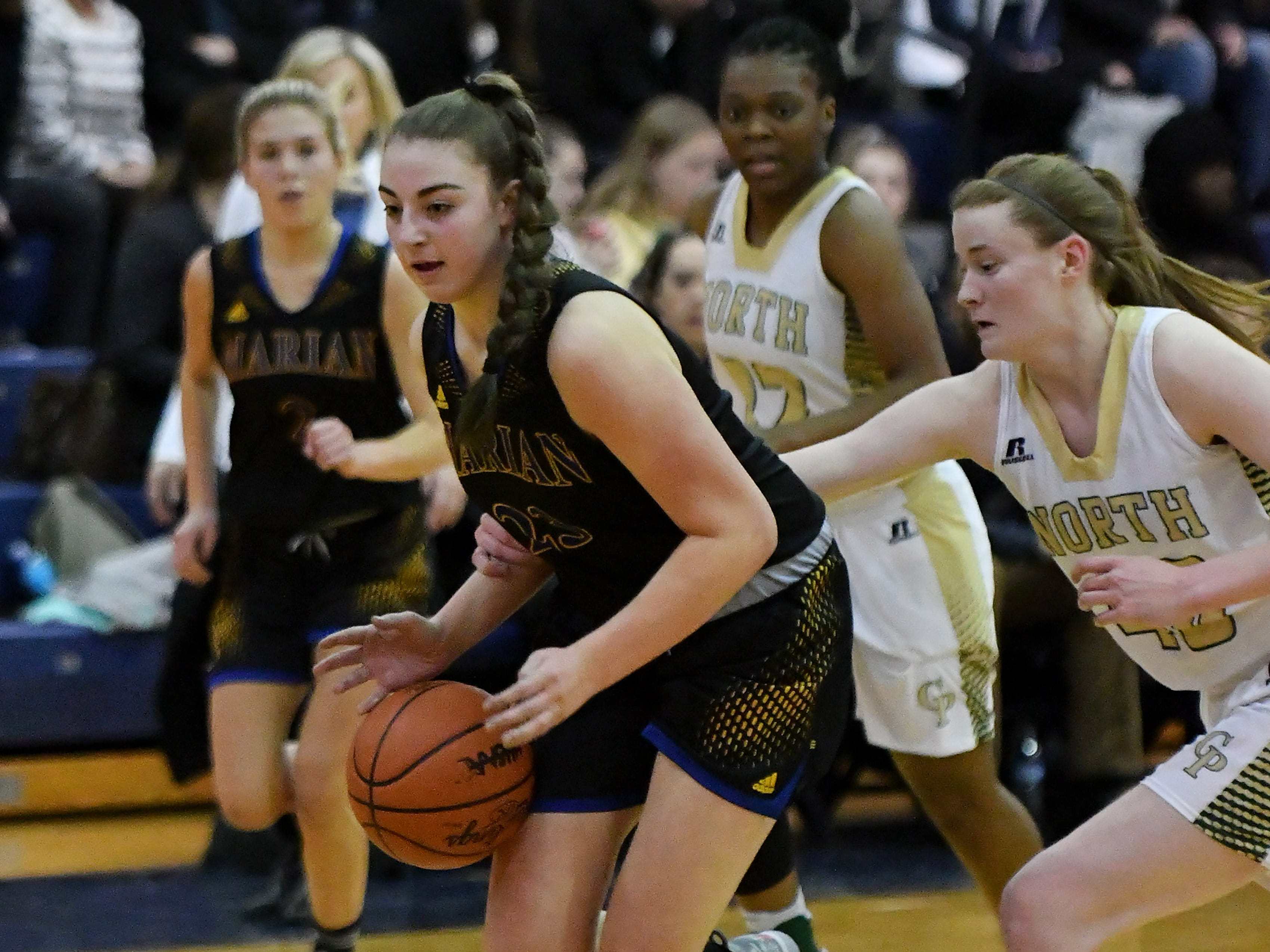 Grosse Pointe North's Julia Ayrault reaches in on Marian's Lauren Licari, left, in the first half.