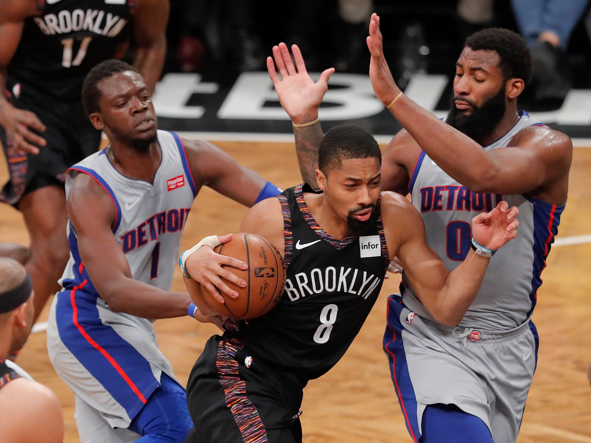 Brooklyn Nets guard Spencer Dinwiddie (8) drives against Detroit Pistons guard Reggie Jackson (1) and Detroit Pistons center Andre Drummond (0) during the third quarter.