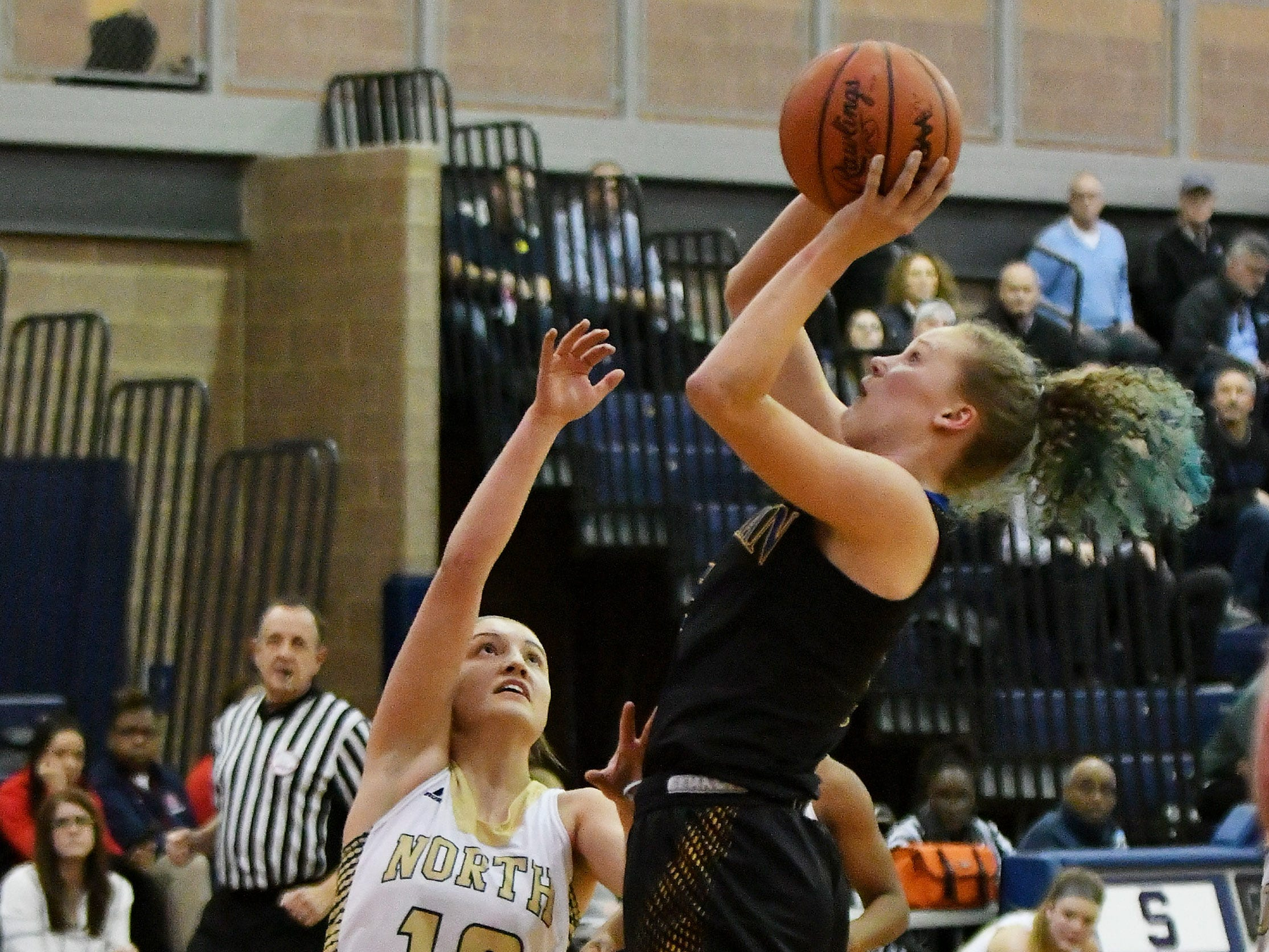 Grosse Pointe North's Evelyn Zacharias (10) defends a shot by Marian's Megan Kraus in the first half.