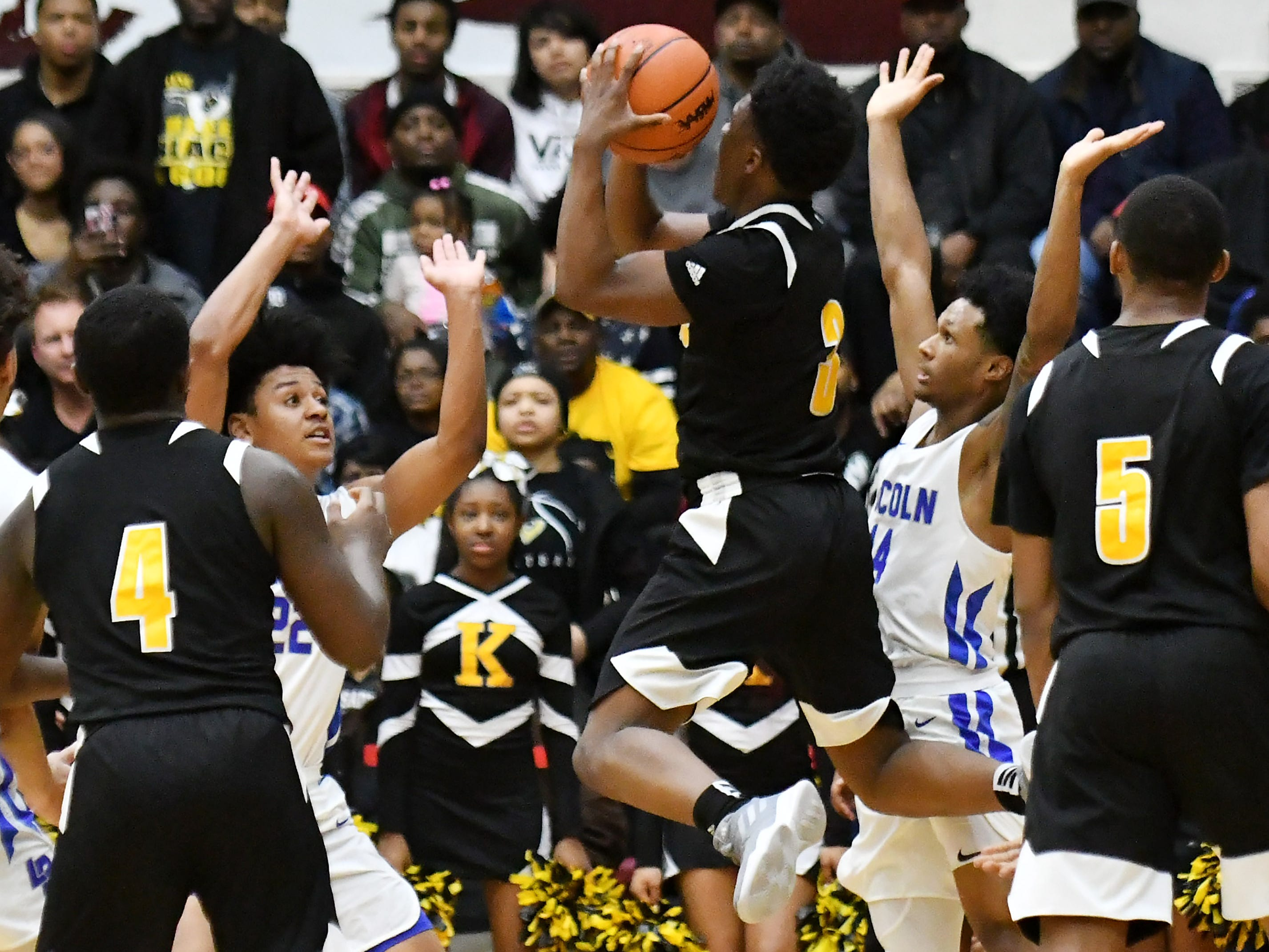 Lincoln's Ibn Abdul-Rahman, left, and Jalen Fisher, right, are careful not to foul King's Jordan Whitford taking King's last shot of the game in the second half.