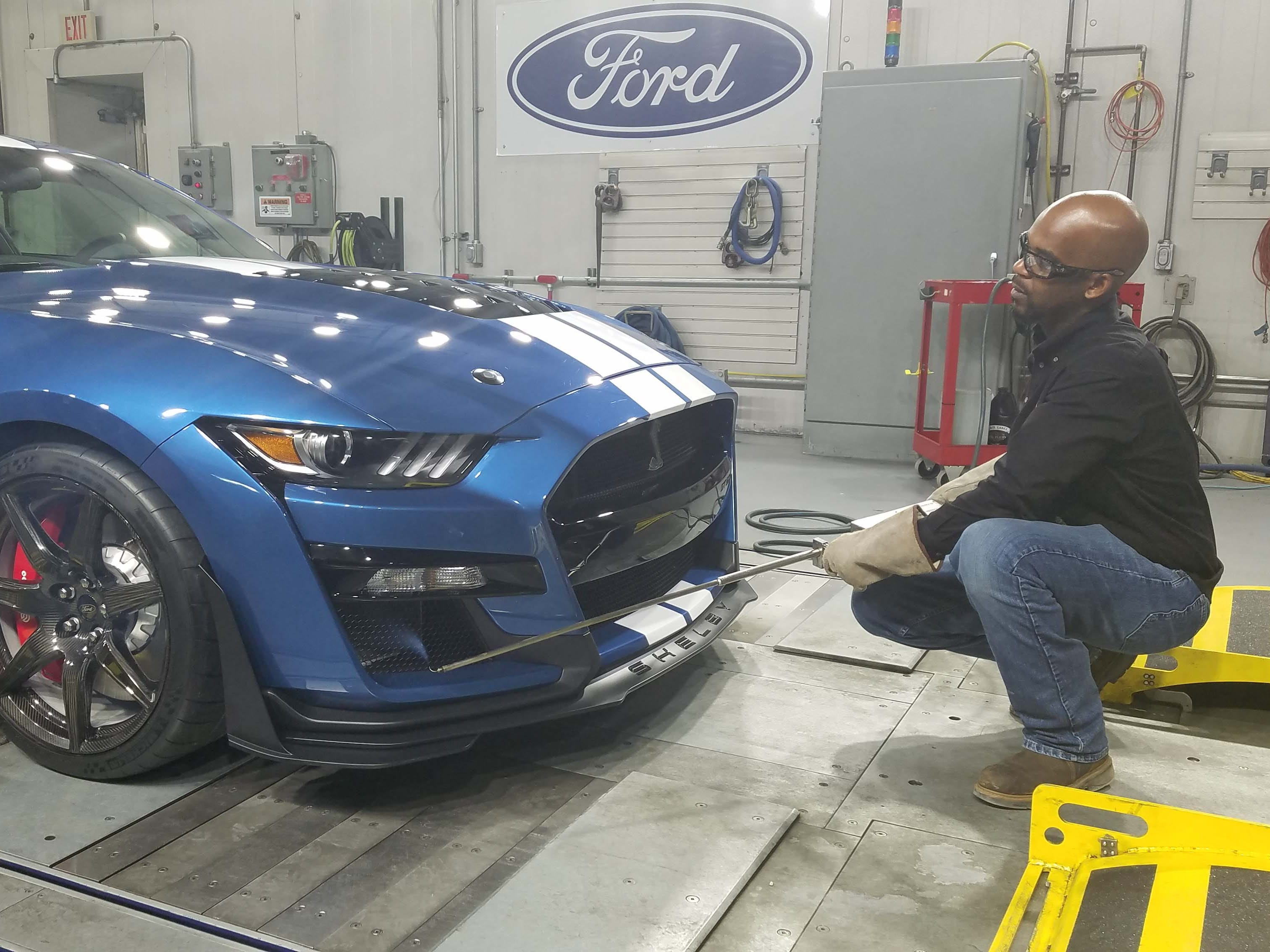 A ford technician demonstrates win tunnel techniques used to evaluate airflow through the 2020 Ford Mustang GT500's front splitter - allowing for better downforce on track - and better cooling for the engine.
