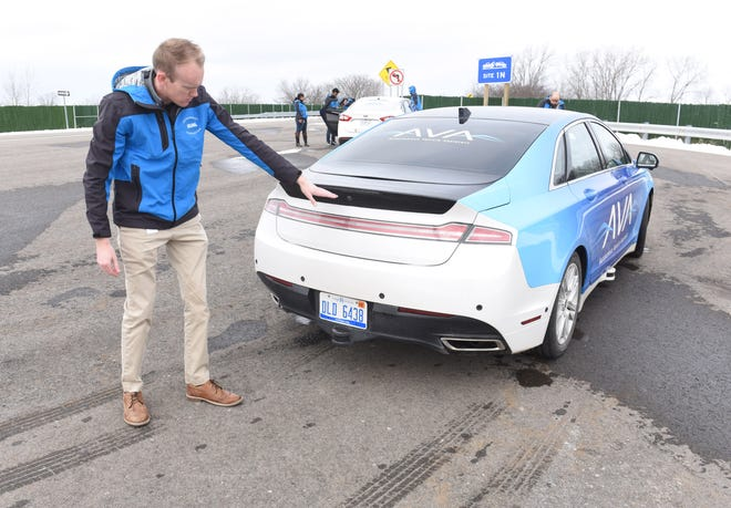 Robert Hoffman, chief engineer, Autonomous Vehicle Functions, DURA, points out ultrasonic sensors around the Autonomous Vehicle Assistant at the American Center for Mobility testing center in Ypsilanti.​​​​​​​ A new consortium is being formed to establish safety principles for driverless cars.