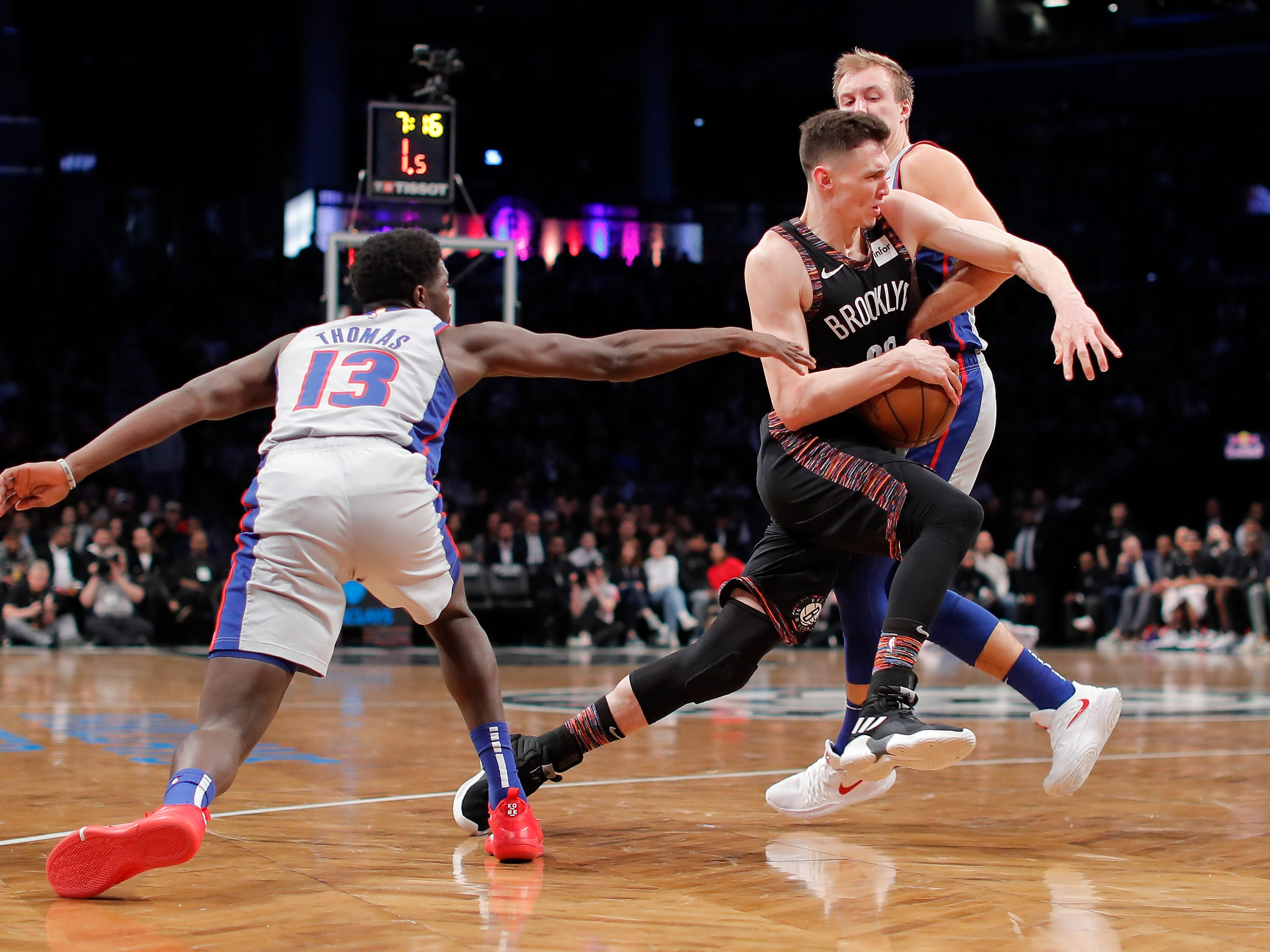 Brooklyn Nets forward Rodions Kurucs (00) drives against Detroit Pistons guard Khyri Thomas (13) and guard Luke Kennard (5) during the fourth quarter.