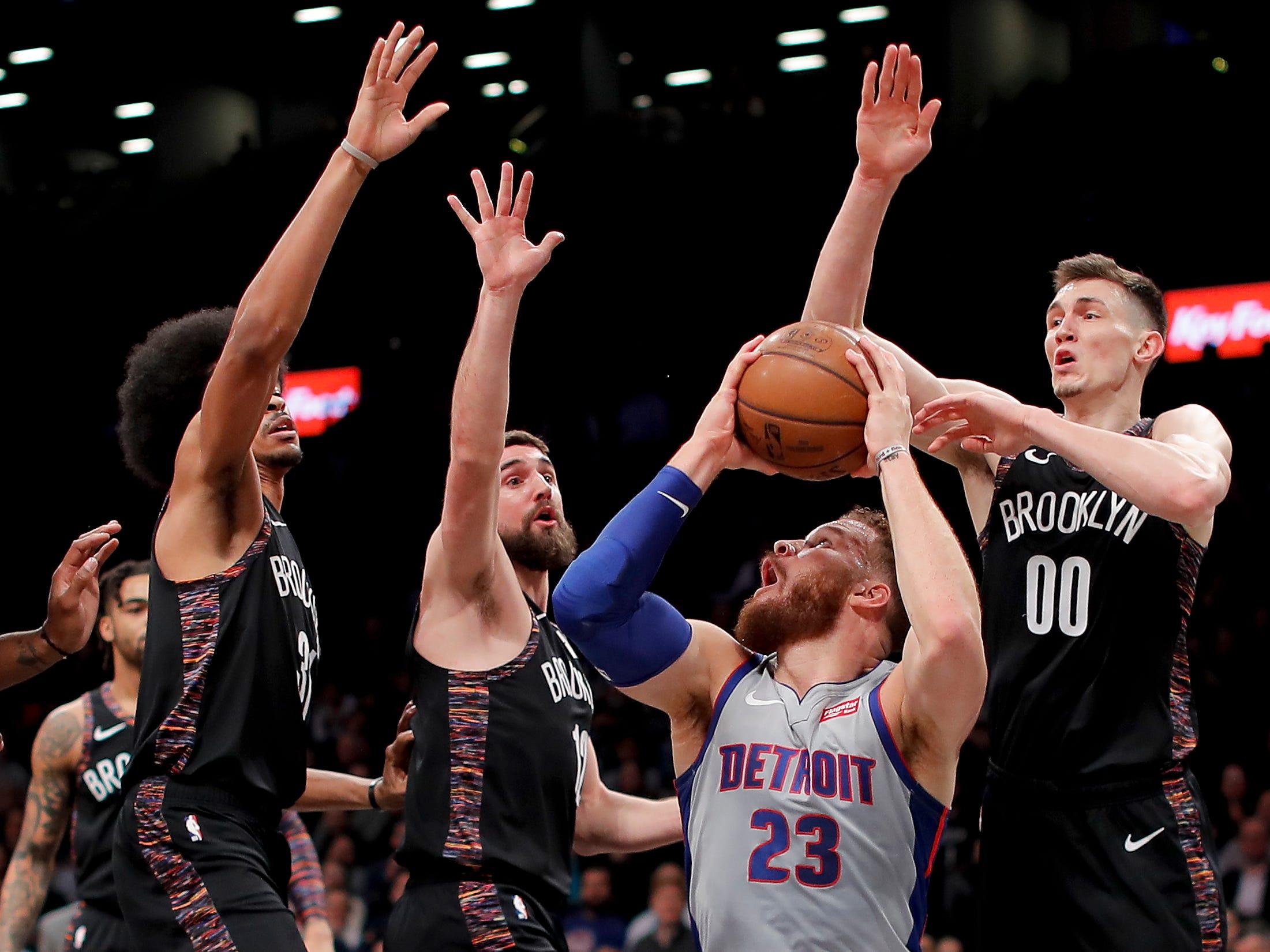Detroit Pistons forward Blake Griffin (23) pump-fakes before shooting against Brooklyn Nets center Jarrett Allen (31), forward Joe Harris (12) and forward Rodions Kurucs (00) during the first quarter.