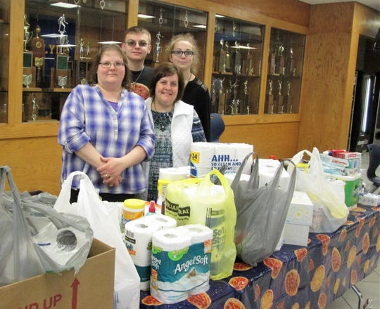 Sisters Brenda Fisher and Theresa Herman, in front stand with Fisher's children Alex and Lizzie along with a table of items donated to the Back Door Food Pantry in 2018.