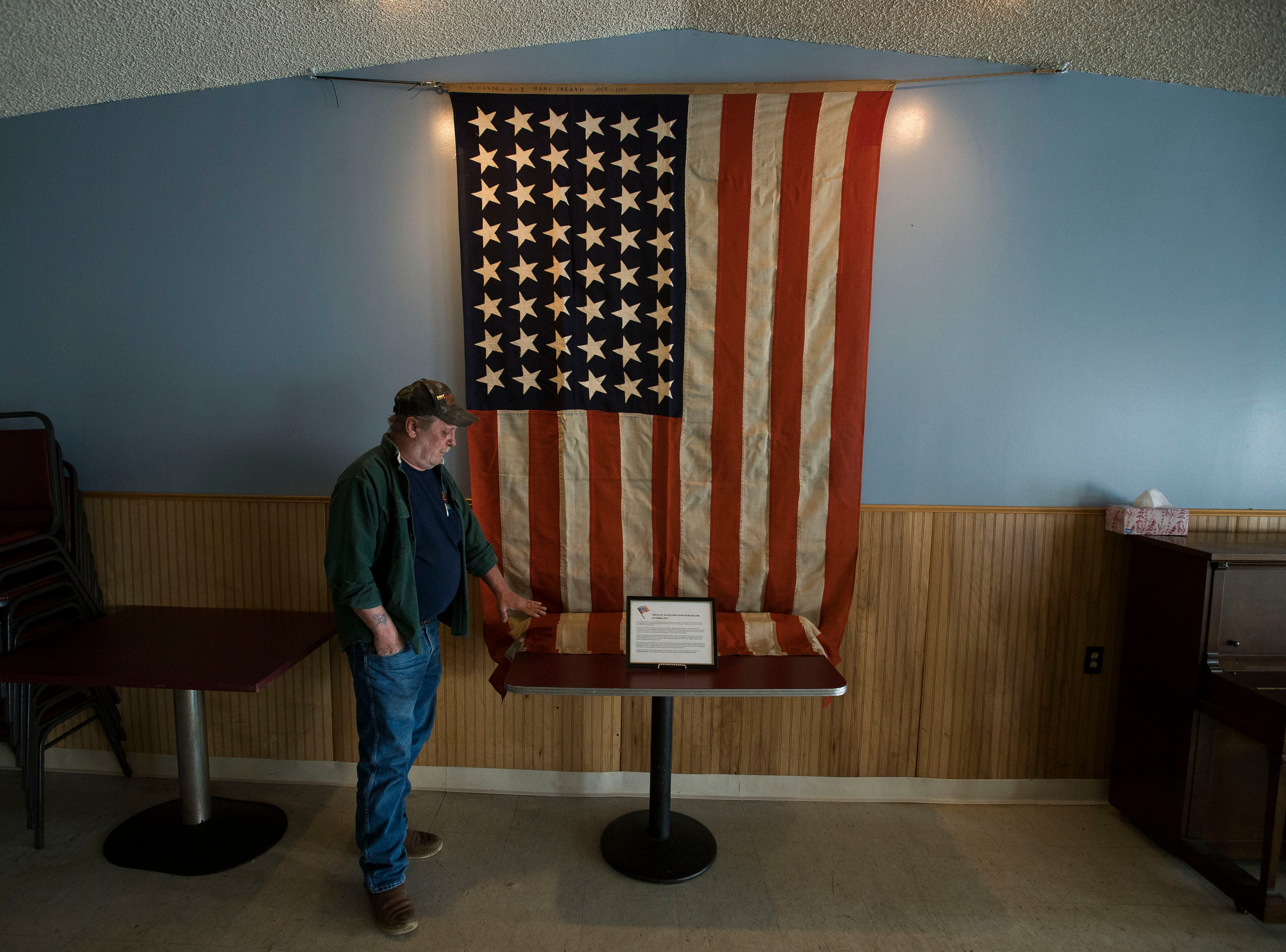 "Jay ""Ziggy"" Ziegler shows the flag that flew at Mare Island in October of 1919, now hanging on the wall on Tuesday, March 12, 2019, at the American Legion Post Four in Fort Collins, Colo."
