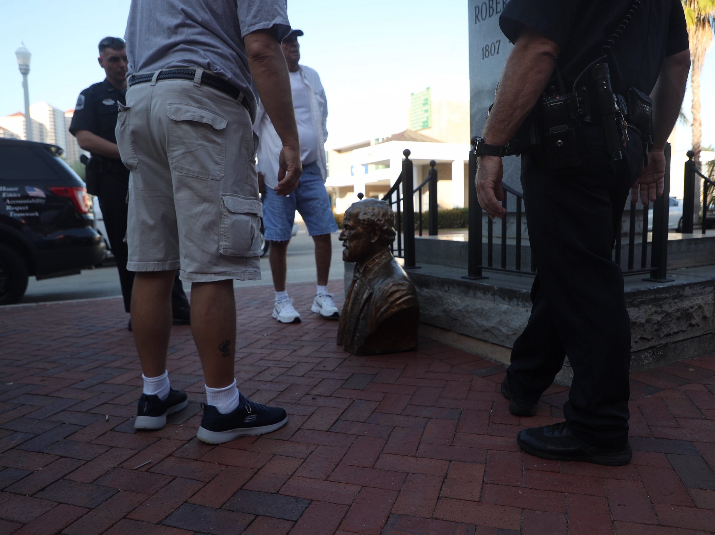 Members of the Fort Myers Police Department and members of the Sons of Confederate Veterans were at the scene of the toppled Robert E. Lee bust in downtown Fort Myers on Tuesday, March 12, 2019. It was found on the ground. The police are investigating.