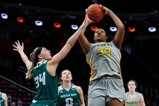 Wright State center Tyler Frierson (33) shoots as UWGB forward Carly Mohns (34) defends in the first half of the Horizon League title game  Tuesday in Detroit.