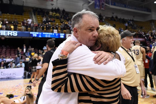 Wofford head coach Mike Young, left, hugs his mother, Nancy Young after his team defeated UNC-Greensboro for the Southern Conference tournament championship, Monday, March 11, 2019, in Asheville, N.C. (AP Photo/Kathy Kmonicek)