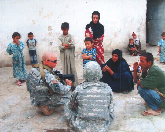 Then-Sgt. Travis Atkins speaks with locals in Iraq, 2007.