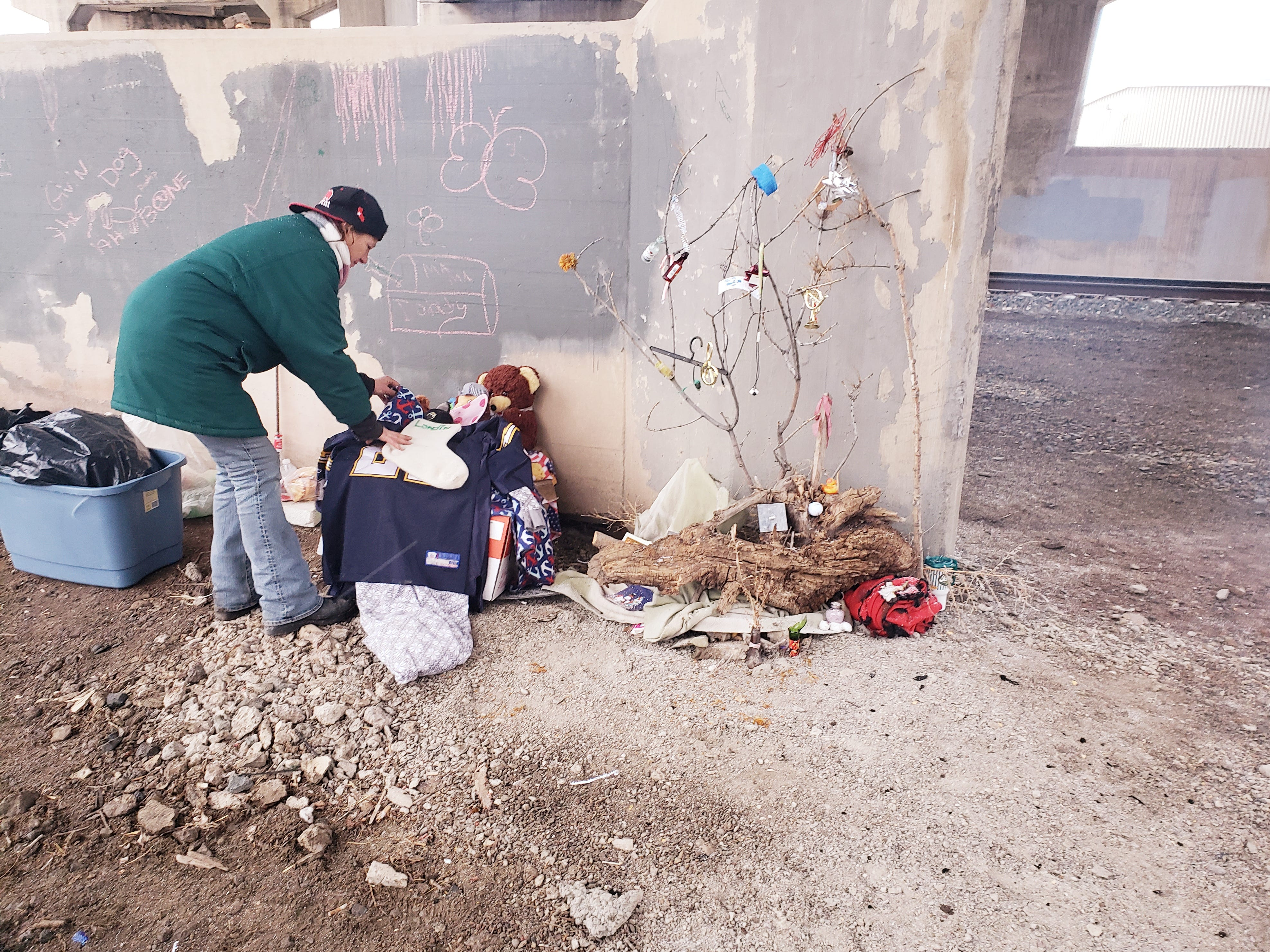 """Barbara Snider arranges decorations in her """"home"""" under the Warden Street Bridge a month or so before she died. The decorations included a Christmas stocking and a Christmas tree she fashioned out of a tree branch and items she collected including ear buds, a hangar and a tiny whisky bottle."""