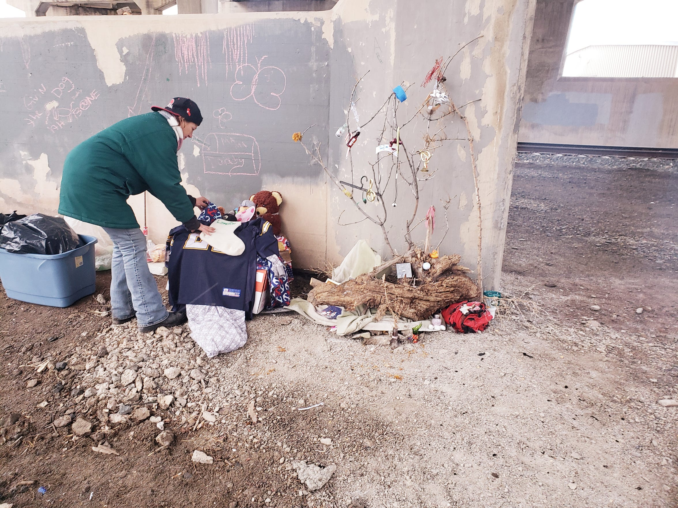 "Barbara Snider arranges decorations in her ""home"" under the Warden Street Bridge a month or so before she died. The decorations included a Christmas stocking and a Christmas tree she fashioned out of a tree branch and items she collected including ear buds, a hangar and a tiny whisky bottle."