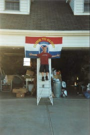 30.	Travis Atkins' son, Trevor Atkins, poses with the 10th Mountain flag at Jack and Elaine's (grandparents') house.