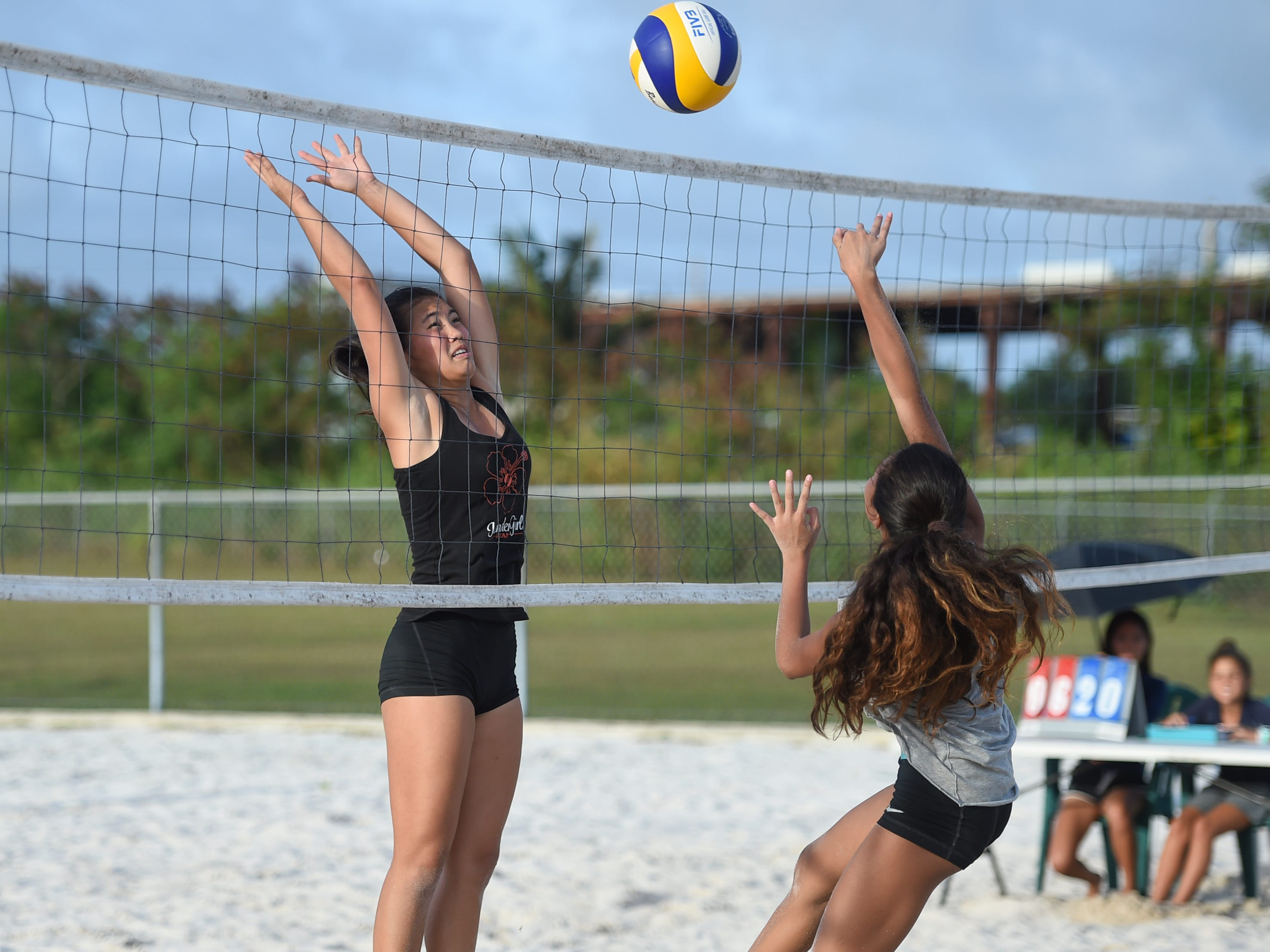 Hallie Wigsten, left, attempts to block a spike from Yasmeen Lopez during the IIAAG Beach Volleyball championship game at the Guam Football Association National Training Center in Dededo, March 12, 2019.