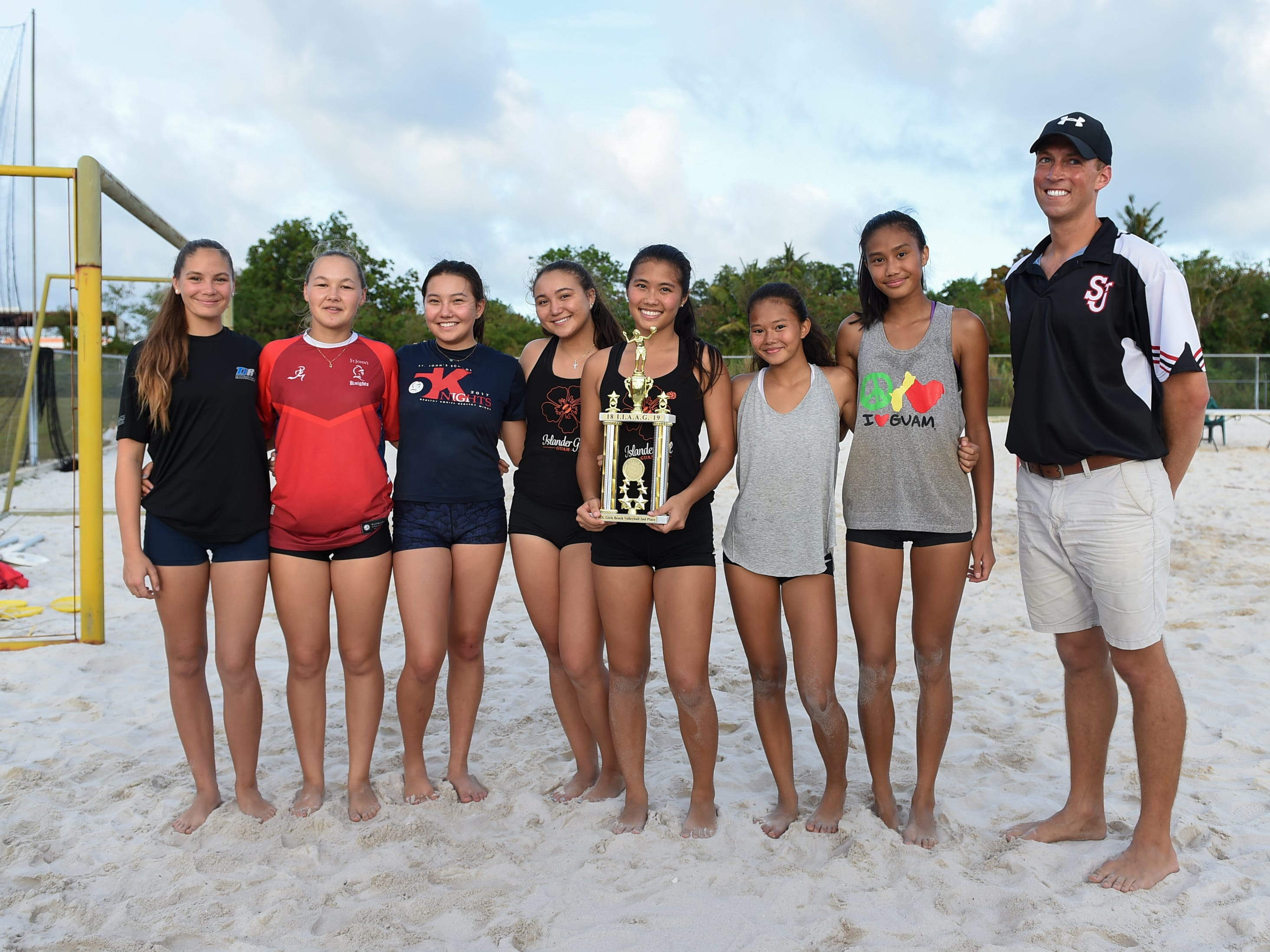 The St. John's White team shares a trophy for their IIAAG Beach Volleyball championship game win at the Guam Football Association National Training Center in Dededo, March 12, 2019.