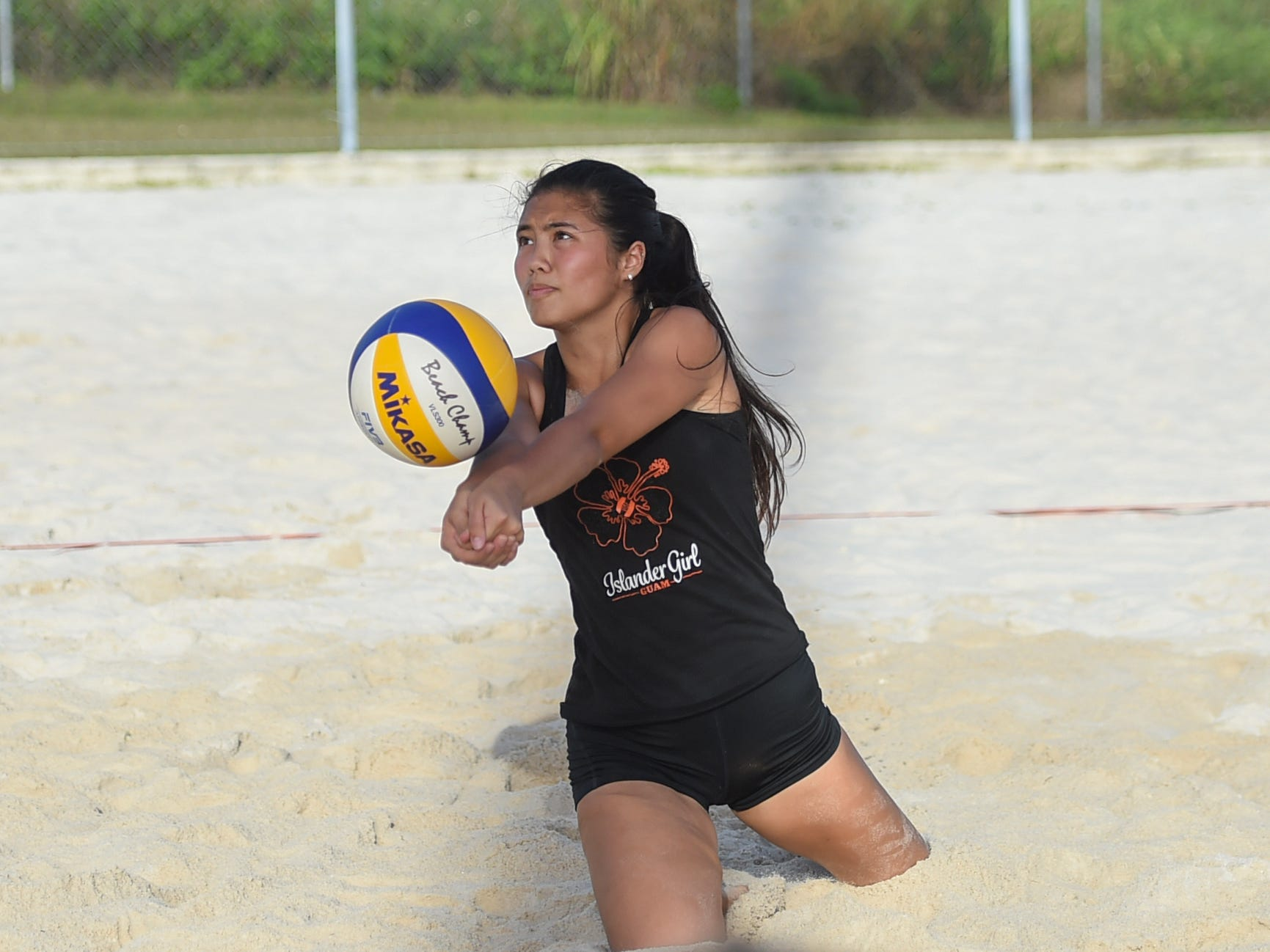 Hallie Wigsten gets low on a bump for her St. John's White team during the IIAAG Beach Volleyball championship game at the Guam Football Association National Training Center in Dededo, March 12, 2019.