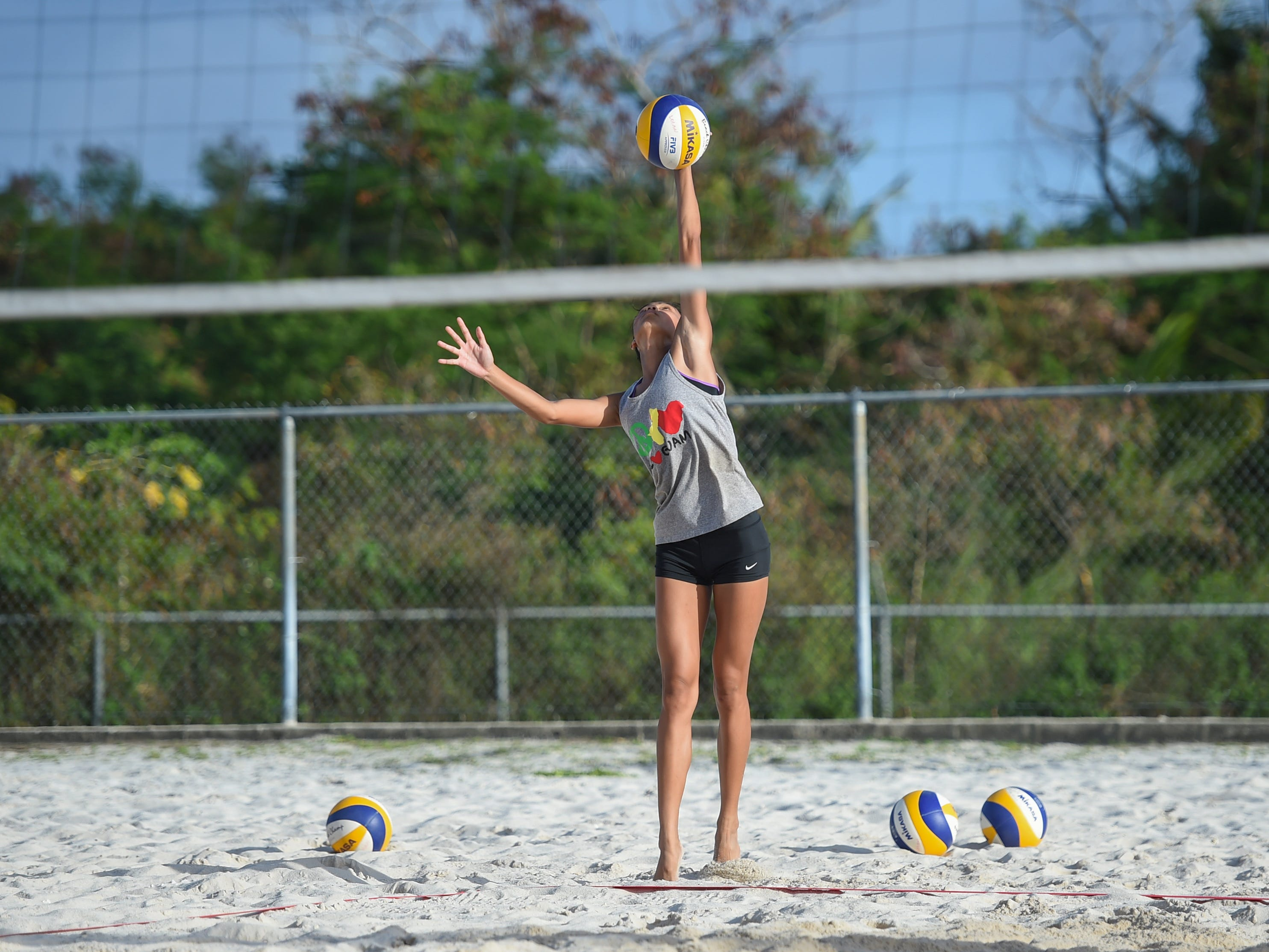 St. John's White's Kristen Serrano serves during the IIAAG Beach Volleyball championship game at the Guam Football Association National Training Center in Dededo