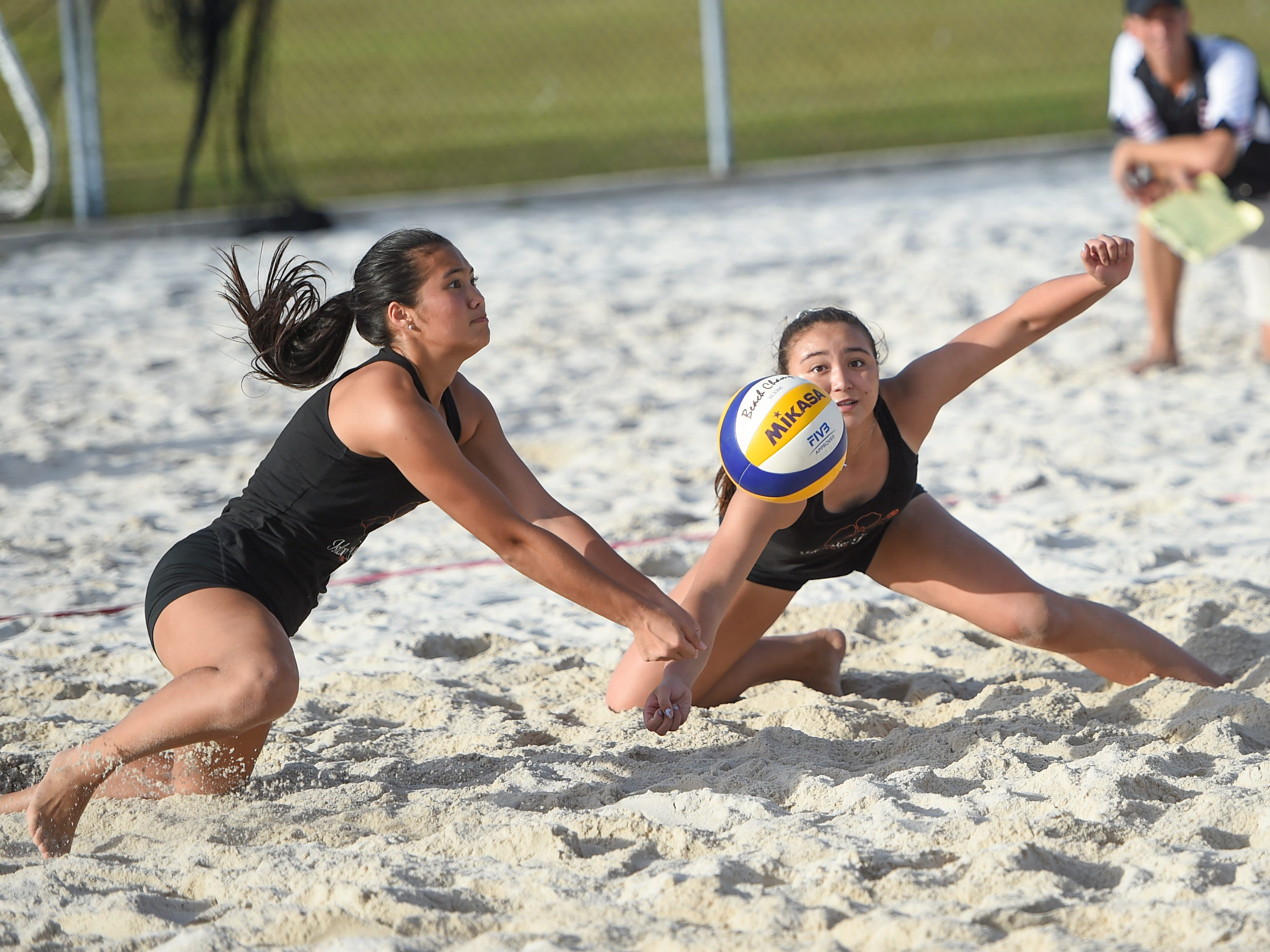 St. John's White teammates Hallie Wigsten, left, and Tylee Shepherd dig on a play during the IIAAG Beach Volleyball championship game at the Guam Football Association National Training Center in Dededo, March 12, 2019.
