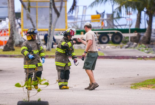 A Guam Fire Department firefighter and a member of the Navy's Explosive Ordnance Disposal Mobile Unit 5 fist bumps as local and federal law enforcement agencies prepare to wrap up their initial investigation of a suspicious device found outside the Guam Fire Department Rescue Base at the Agat Marina compound on Tuesday, March 12, 2019.
