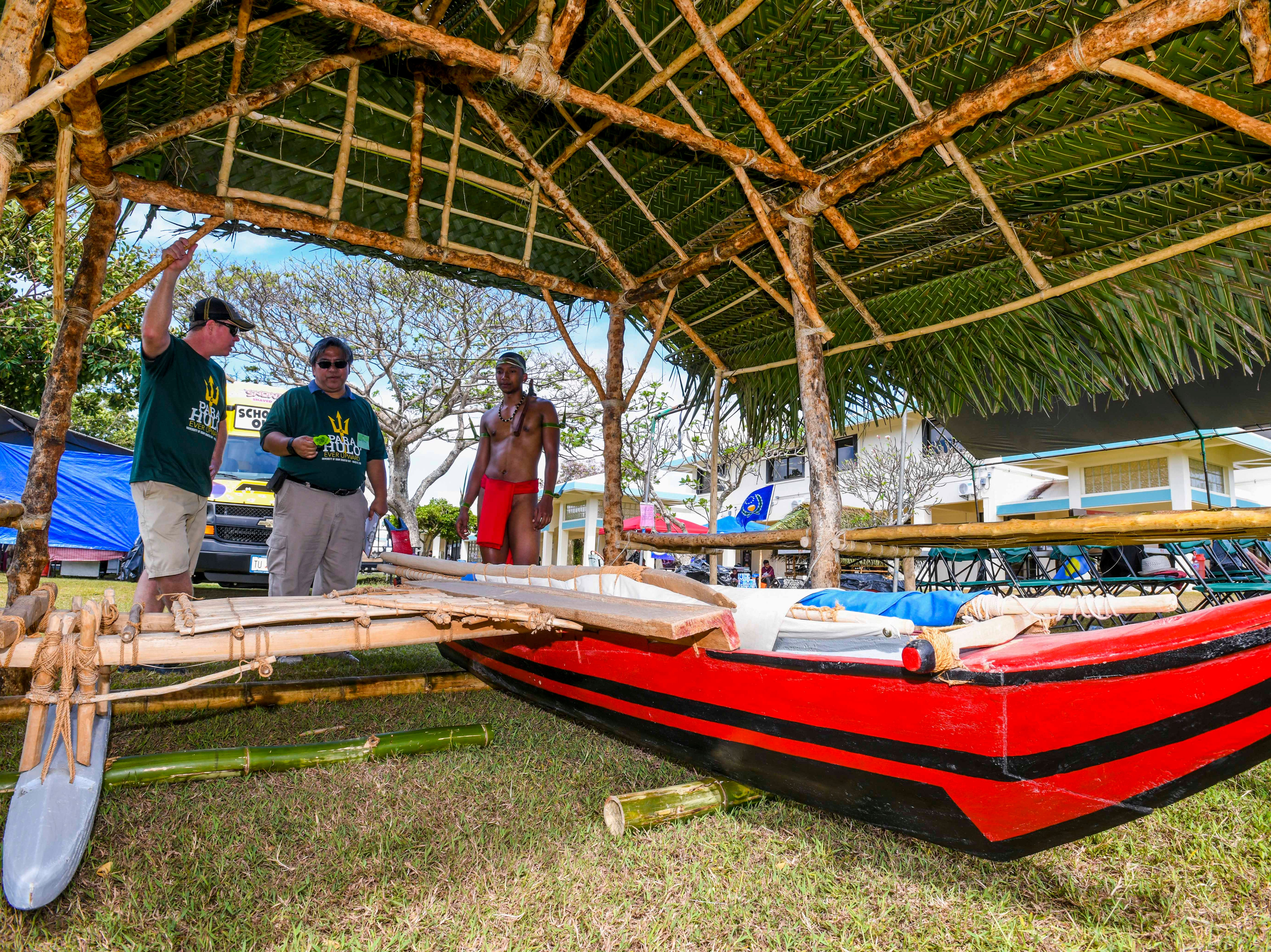Chalan Pago-Ordot Mayor Jessy Gogue, center, inquires information about an outrigger canoe from marine biology student Alexander Rudimch, right, as he judges huts built by student organizations for the University of Guam's 51st Charter Day in Mangilao on Tuesday, March 12, 2019. Rudimch was representing the students from the Republic of Palau.
