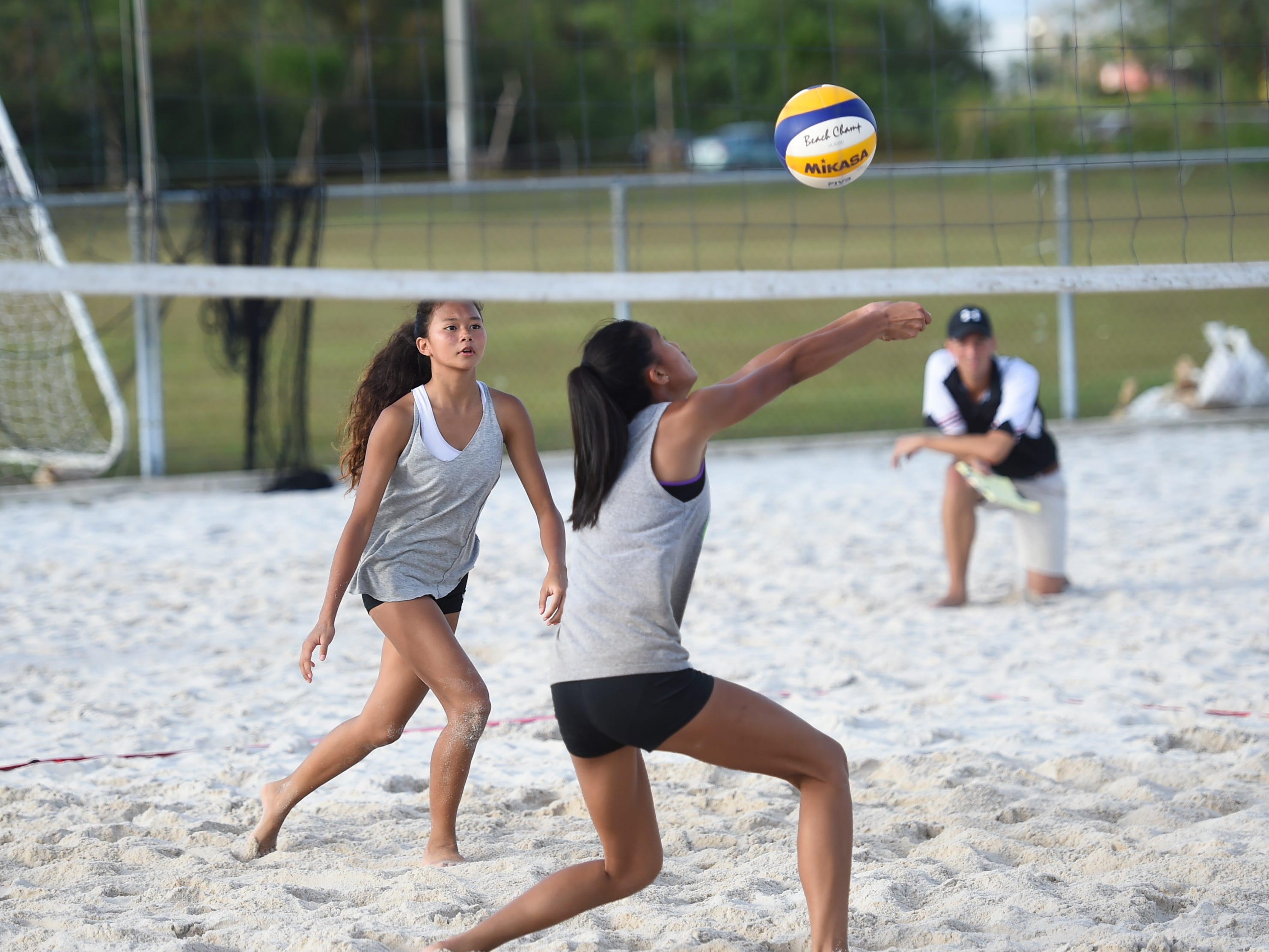 St. John's teammates Kristen Serrano, right, and Yasmeen Lopez setup a play during the IIAAG Beach Volleyball championship game at the Guam Football Association National Training Center in Dededo, March 12, 2019.