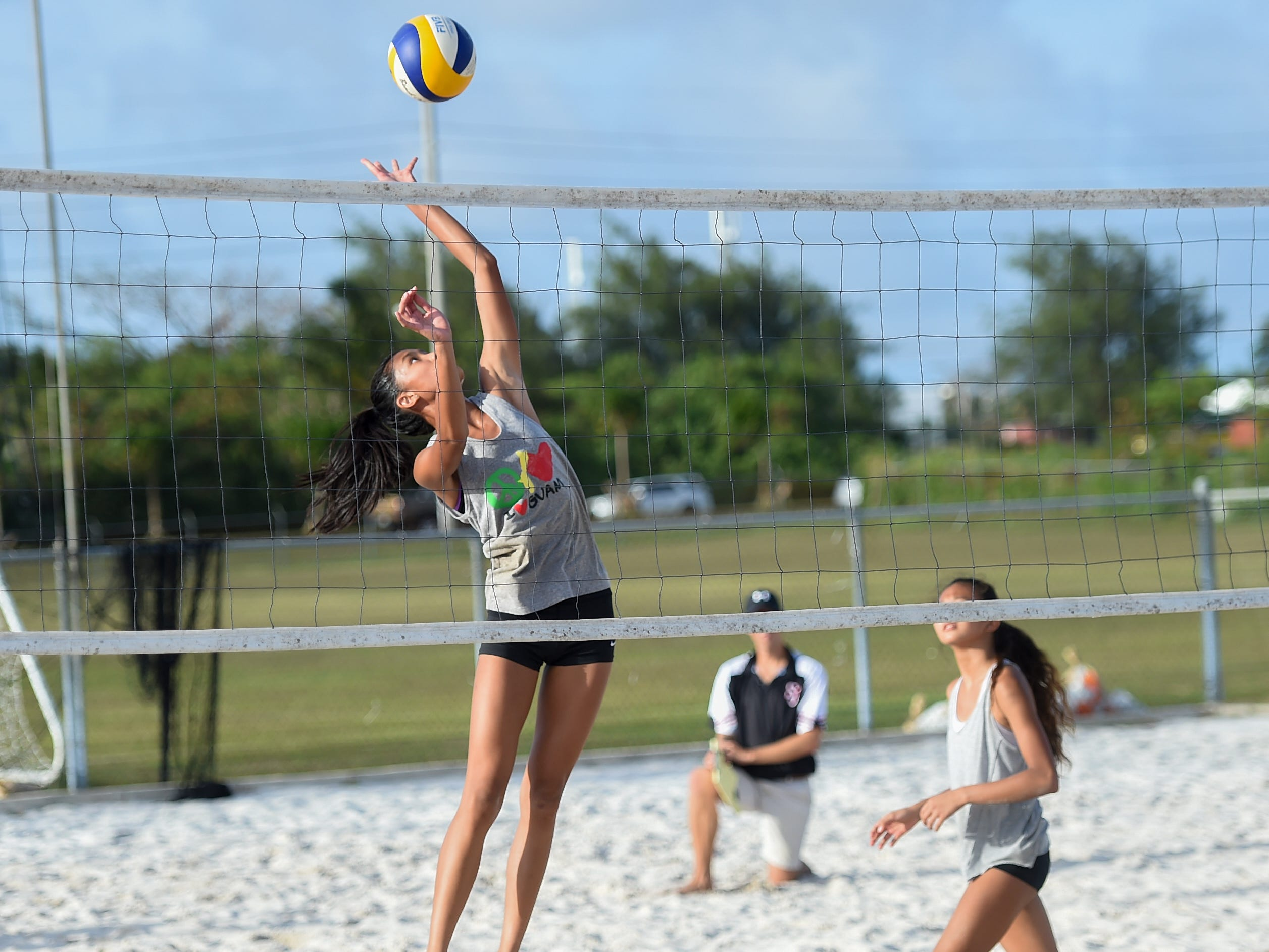 St. John's player Kristen Serrano jumps to spike during the IIAAG Beach Volleyball championship game at the Guam Football Association National Training Center in Dededo, March 12, 2019.