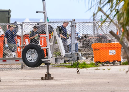 Local and federal law enforcement agency officers can be seen behind a chain-link fence investigating a suspicious device discovered outside the Guam Fire Department Rescue Base at the Agat Marina compound on Tuesday, March 12, 2019. Traffic was closed to travel, near the area on Route 2, for about four hours before the all clear was given and roads reopened for the drivers.