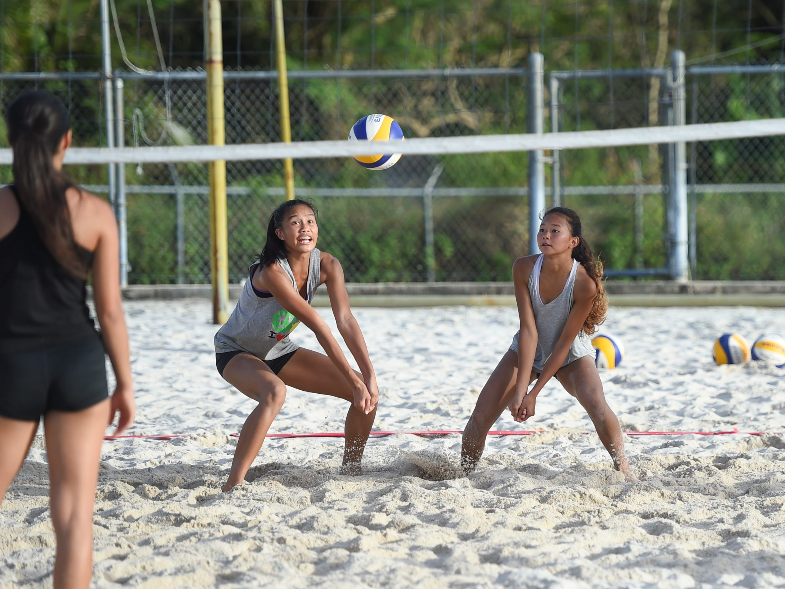 St. John's teammates Yasmeen Lopez, right, and Kristen Serrano look to bump the ball during the IIAAG Beach Volleyball championship game at the Guam Football Association National Training Center in Dededo, March 12, 2019.