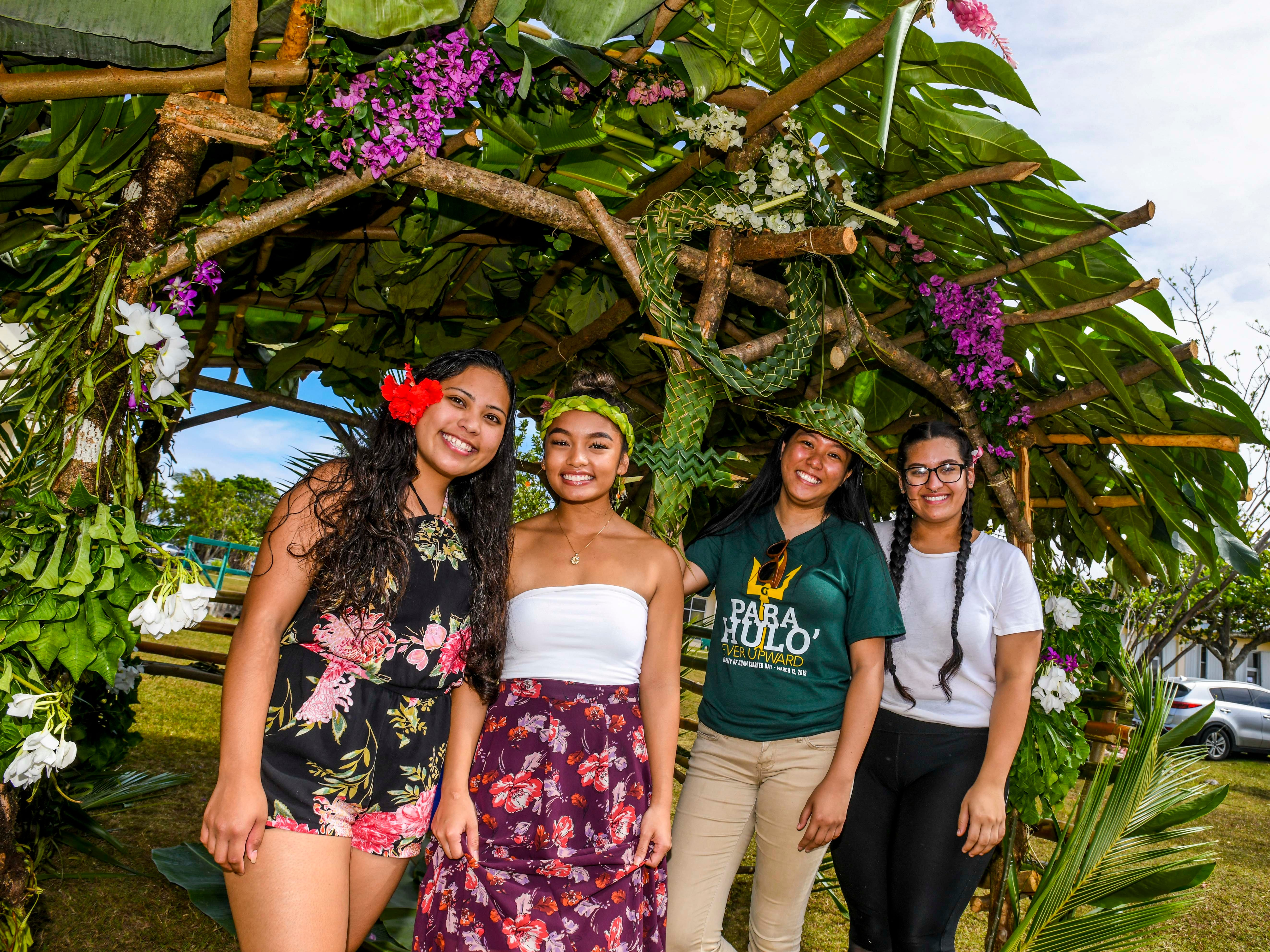 Bali Field School sociology students stand to greet visitors to their hut during the University of Guam's 51st Charter Day celebration in Mangilao on Tuesday, March 12, 2019. The students wanted to especially bring attention to the female symbol to express their feminism, woven from coconut leaves and positioned prominently high at the front of the structure.