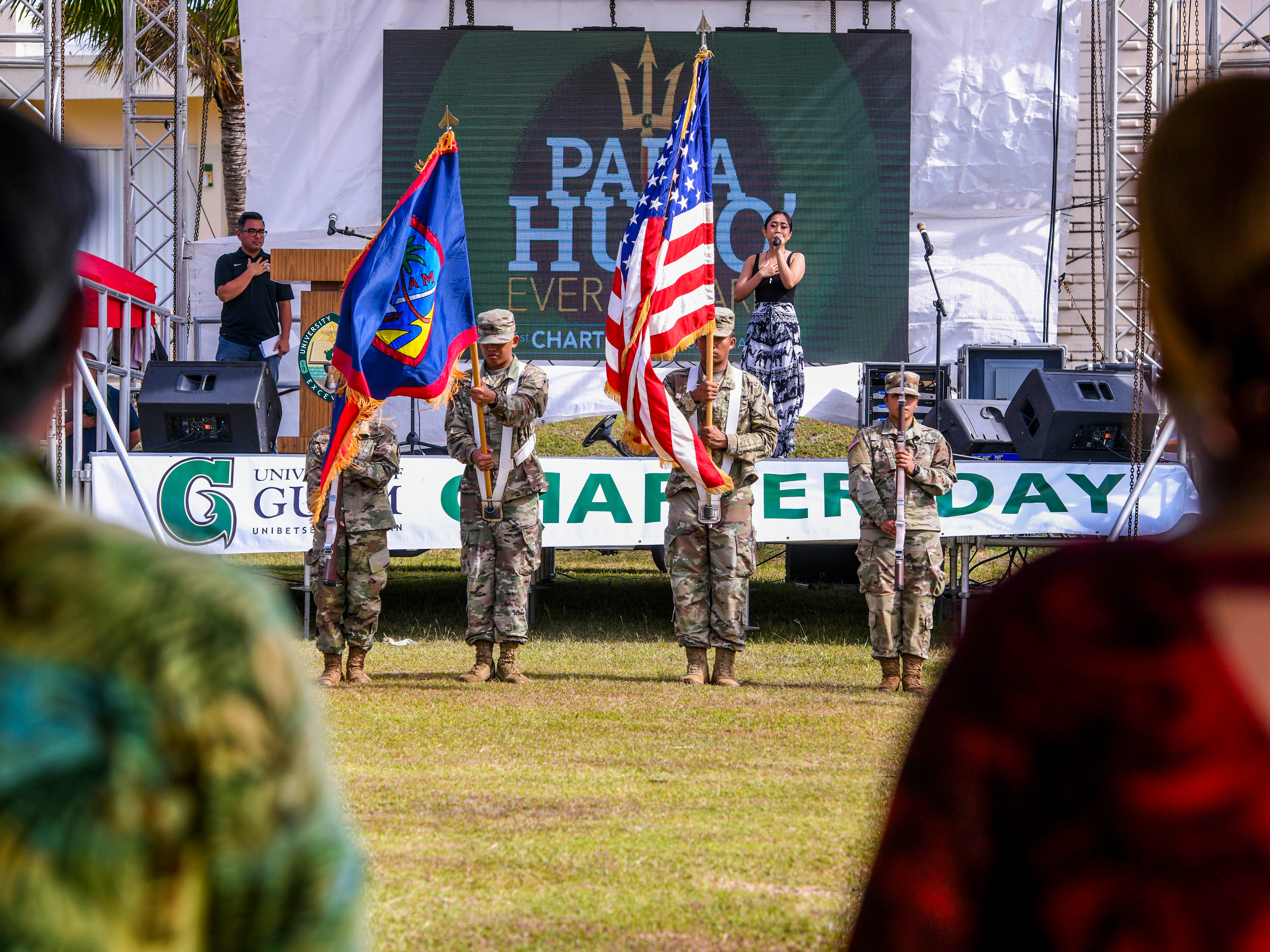 The American and Guam flags are posted by Army ROTC cadets as music student Diane Lubas performs the national anthem during the opening ceremony University of Guam's 51st Charter Day in Mangilao on Tuesday, March 12, 2019.