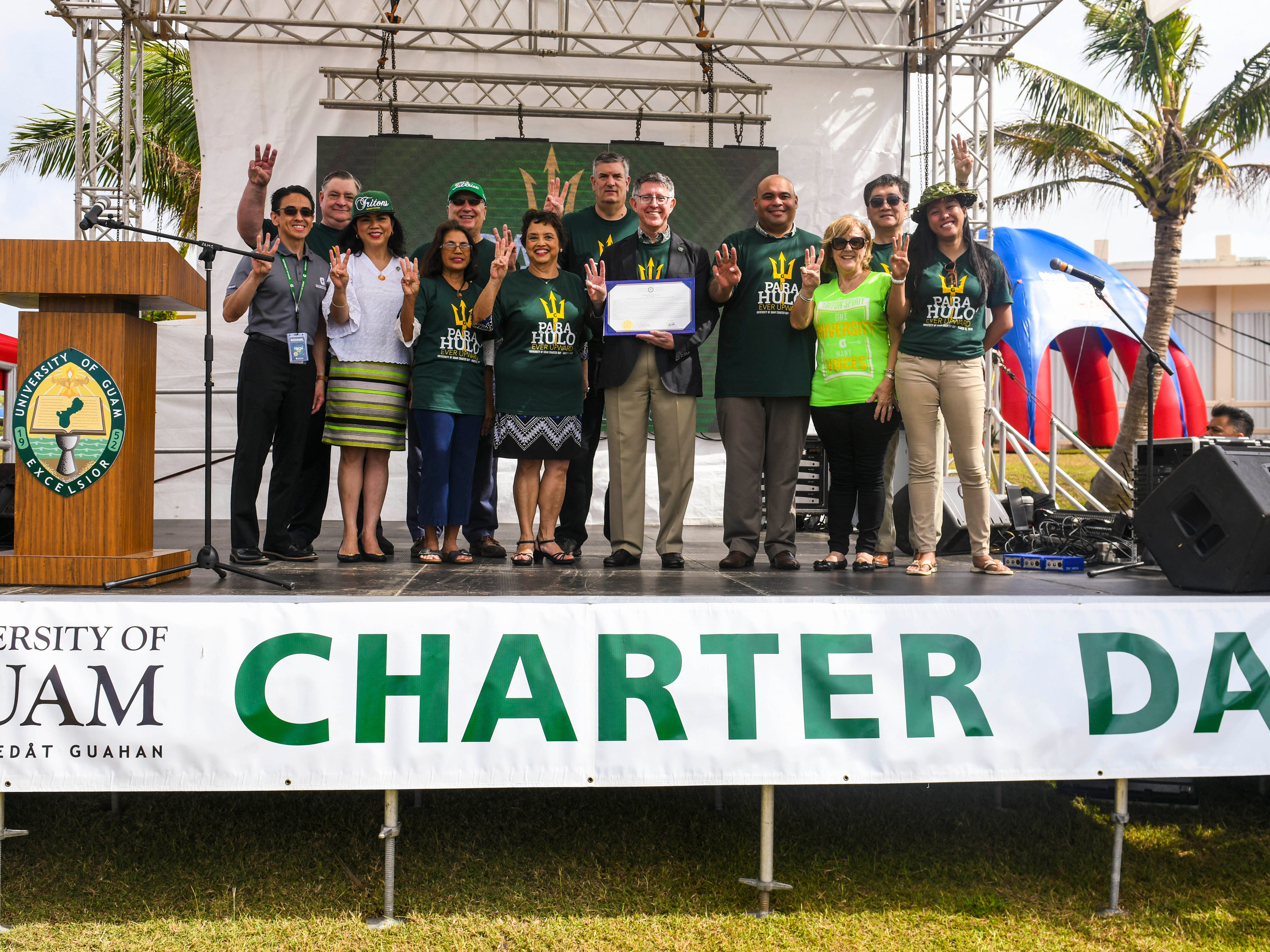 Gov. Lou Leon Guerrero, Lt. Gov. Josh Tenorio, and University of Guam faculty members hold up three fingers, symbolic of the college's triton emblem, after a proclamation signing was held in celebration of UOG's 51st Charter Day in Mangilao on Tuesday, March 12, 2019.