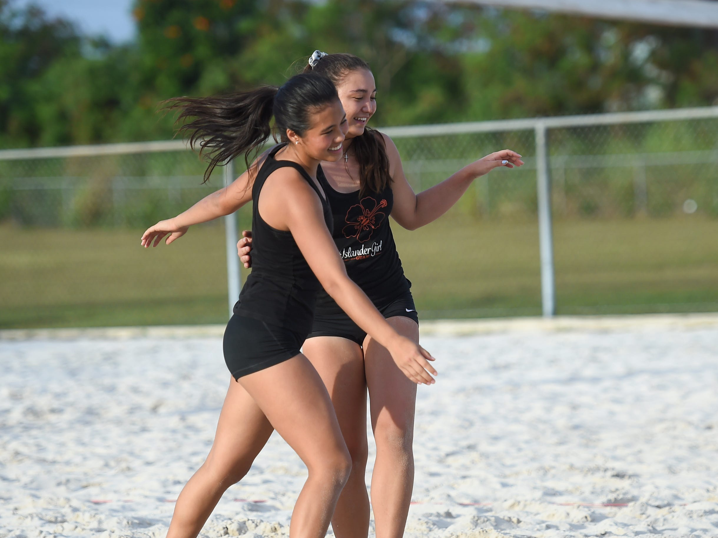 St. John's White teammates Tylee Shepherd, right, and Hallie Wigsten celebrate their IIAAG Beach Volleyball championship game win at the Guam Football Association National Training Center in Dededo, March 12, 2019.
