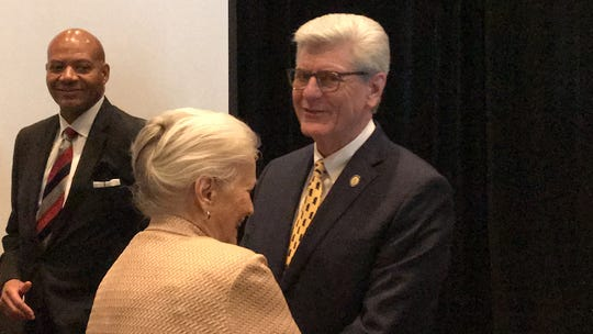 Gov. Phil Bryant laughs with a constituent after an announcement of Kohler Engines' expansion in Hattiesburg.