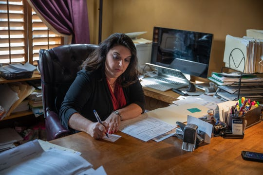 Indianapolis attorney Jynell Berkshire sifts through a pile of notes on her desk inside her home office on Tuesday, March 12, 2019. The notes are from calls she's had with investors concerned about their dealings with Morris Invest and Oceanpointe regarding properties they purchased in Indianapolis.