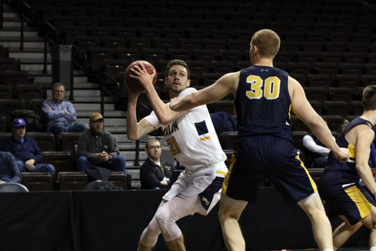 Cameron Wolter of Marian works against the defense by Jeff Beckman of Spring Arbor during Monday's NAIA semifinal game in Sioux Falls, SD.